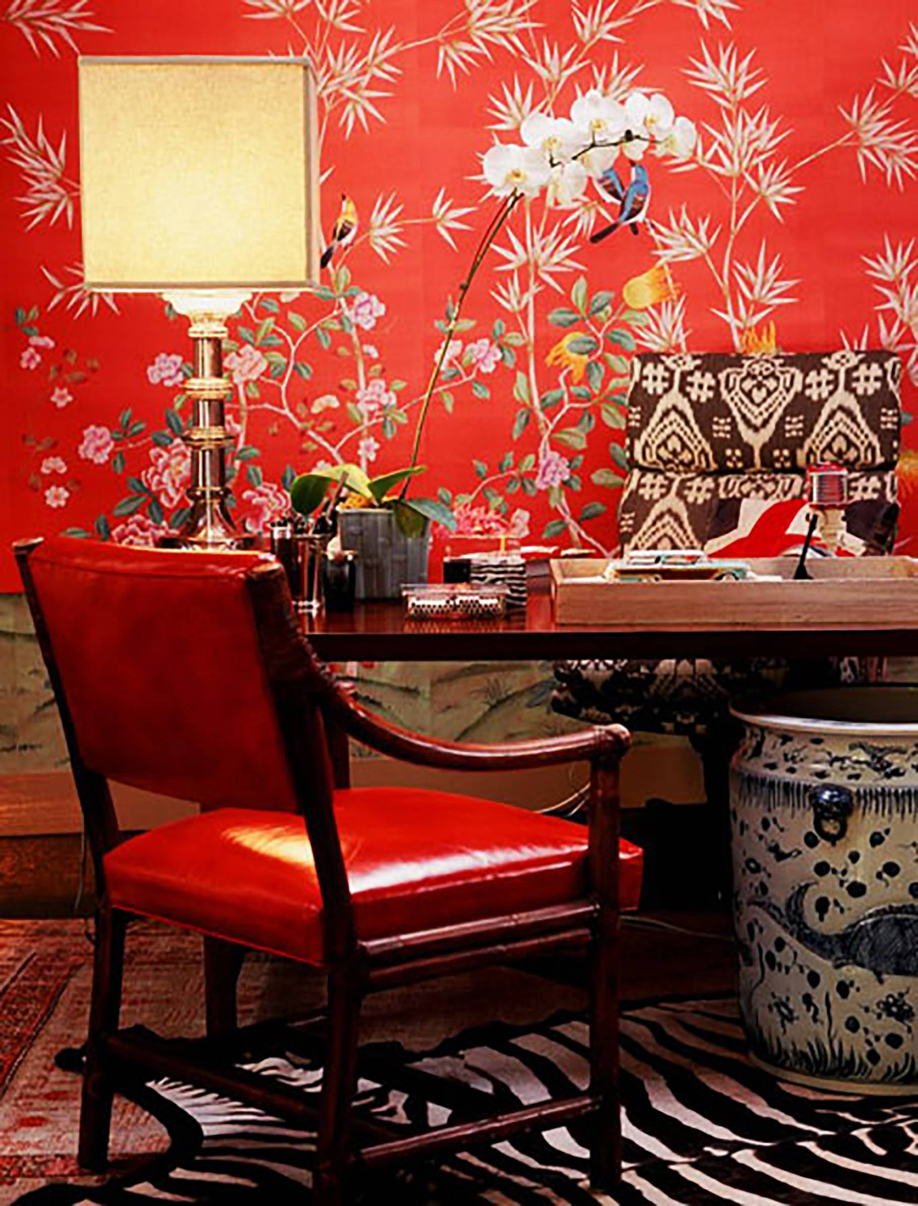 Bold red wallpaper and upholstery are combined with neutral colors to create a lively but cohesive design for this home office.
