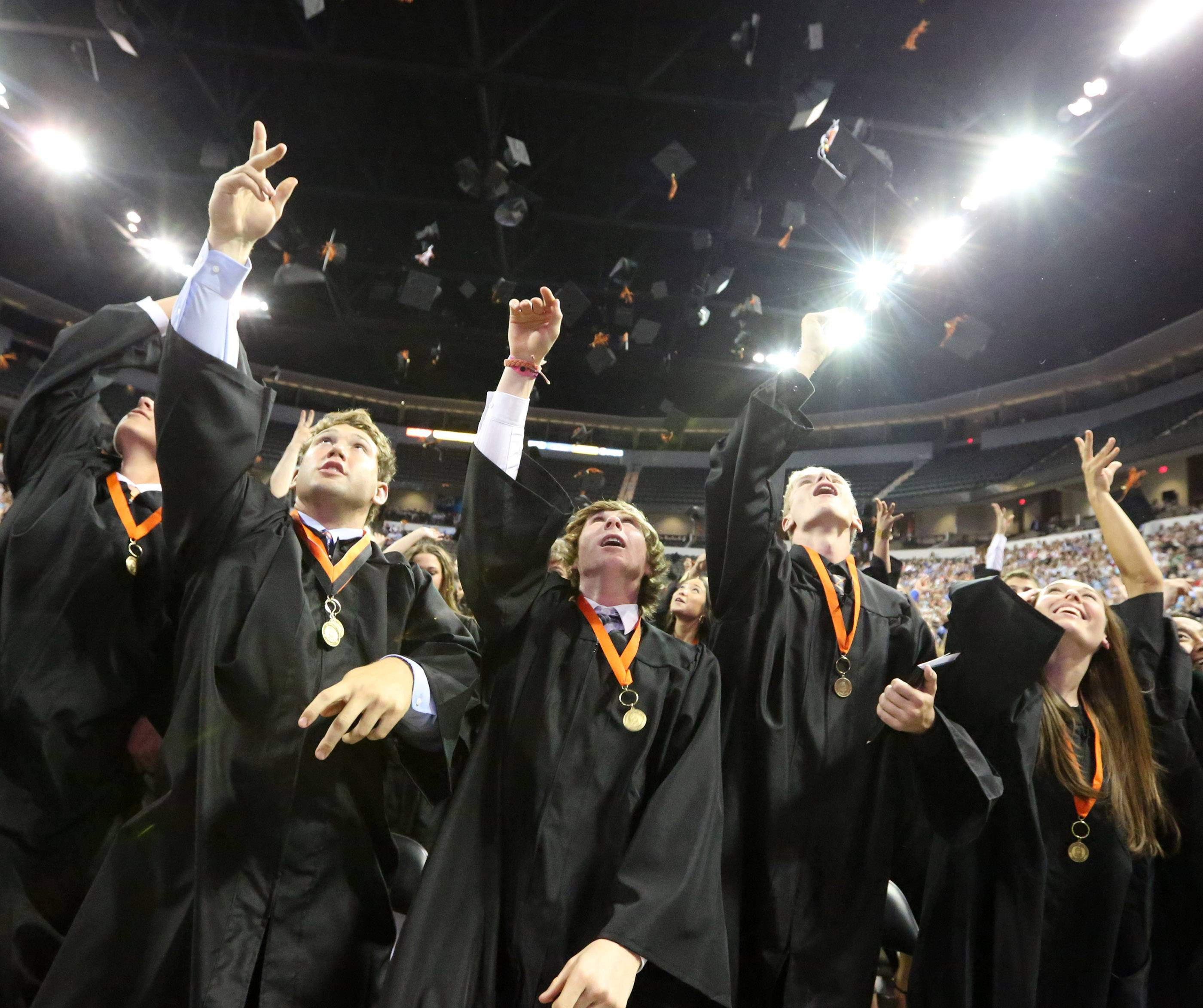 Nick Bagatti, center, and fellow graduates throw their caps in the air .