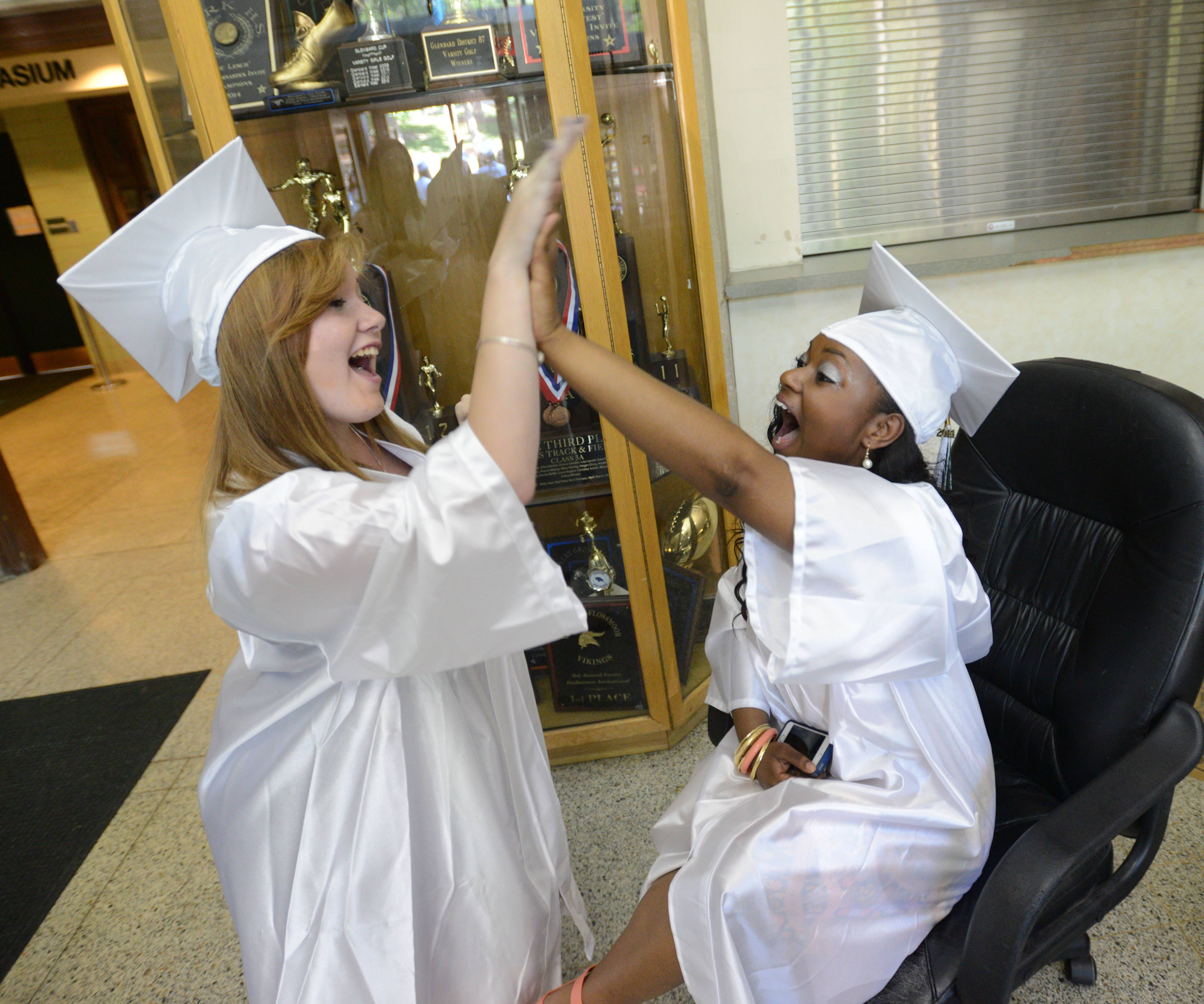 Alyssa O'Brien,18, of Glendale Heights and Kiana Whitley ,18, of Glen Ellyn high five before the Glenbard West High School graduation ceremony Friday.