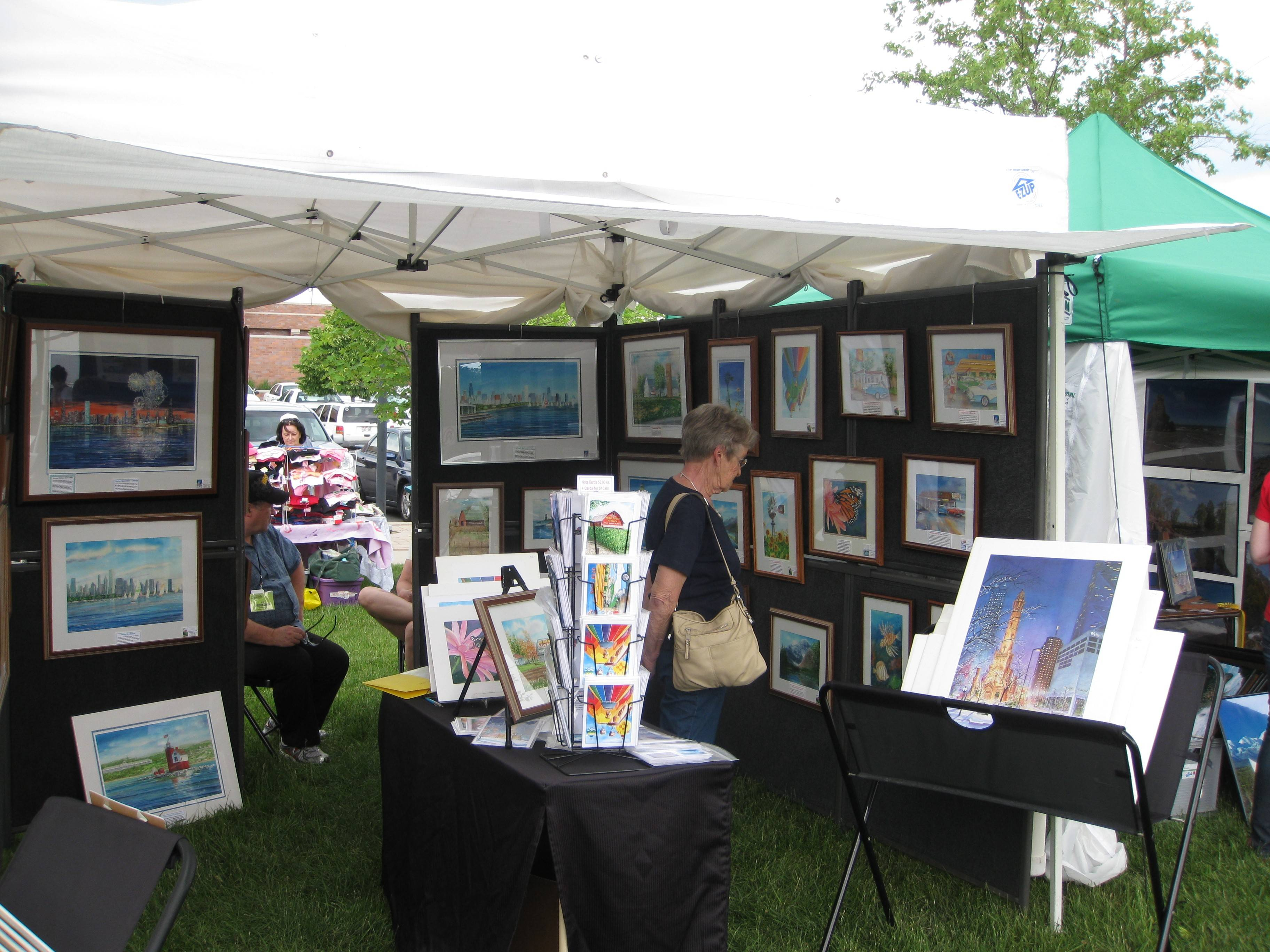 A visitor looks over paintings in one artist's tent, at a previous Art in the Park in Elk Grove Village.