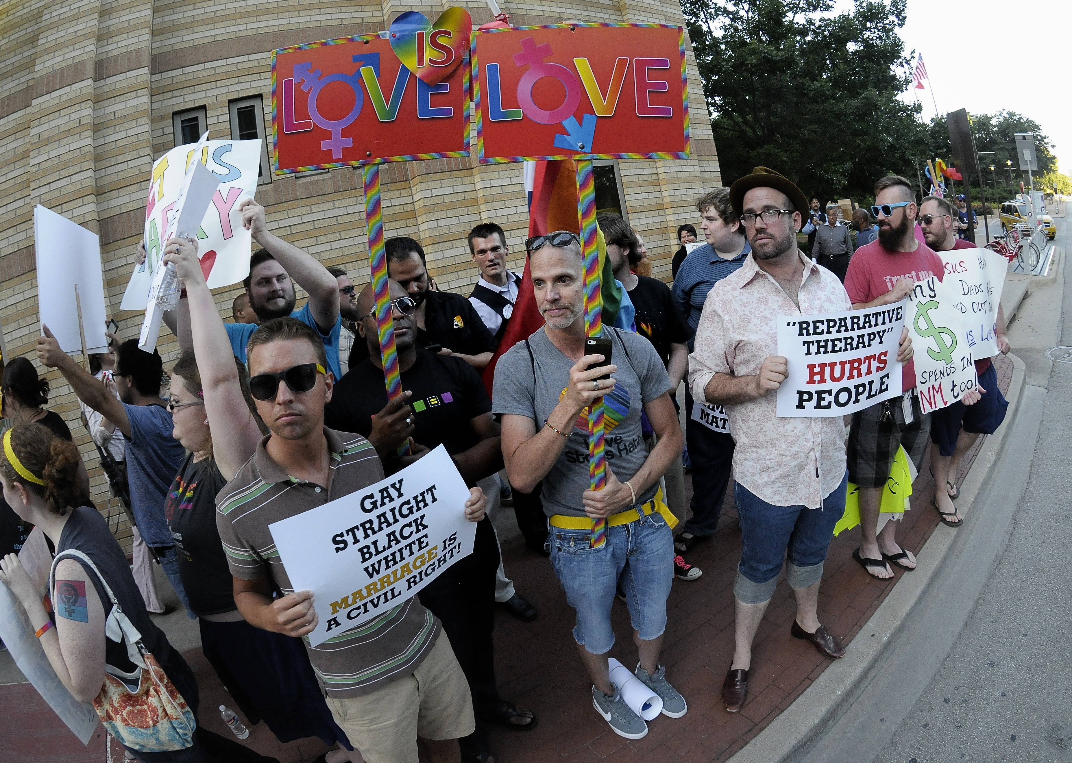 "People hold signs during a same-sex marriage rally outside the Fort Worth Convention Center in Fort Worth, Texas, Thursday, June 5, 2014. The Texas Republican Party would endorse psychological treatment that seeks to turn gay people straight under a new platform partly aimed at rebuking laws in California and New Jersey that ban so-called ""reparative therapy"" on minors."
