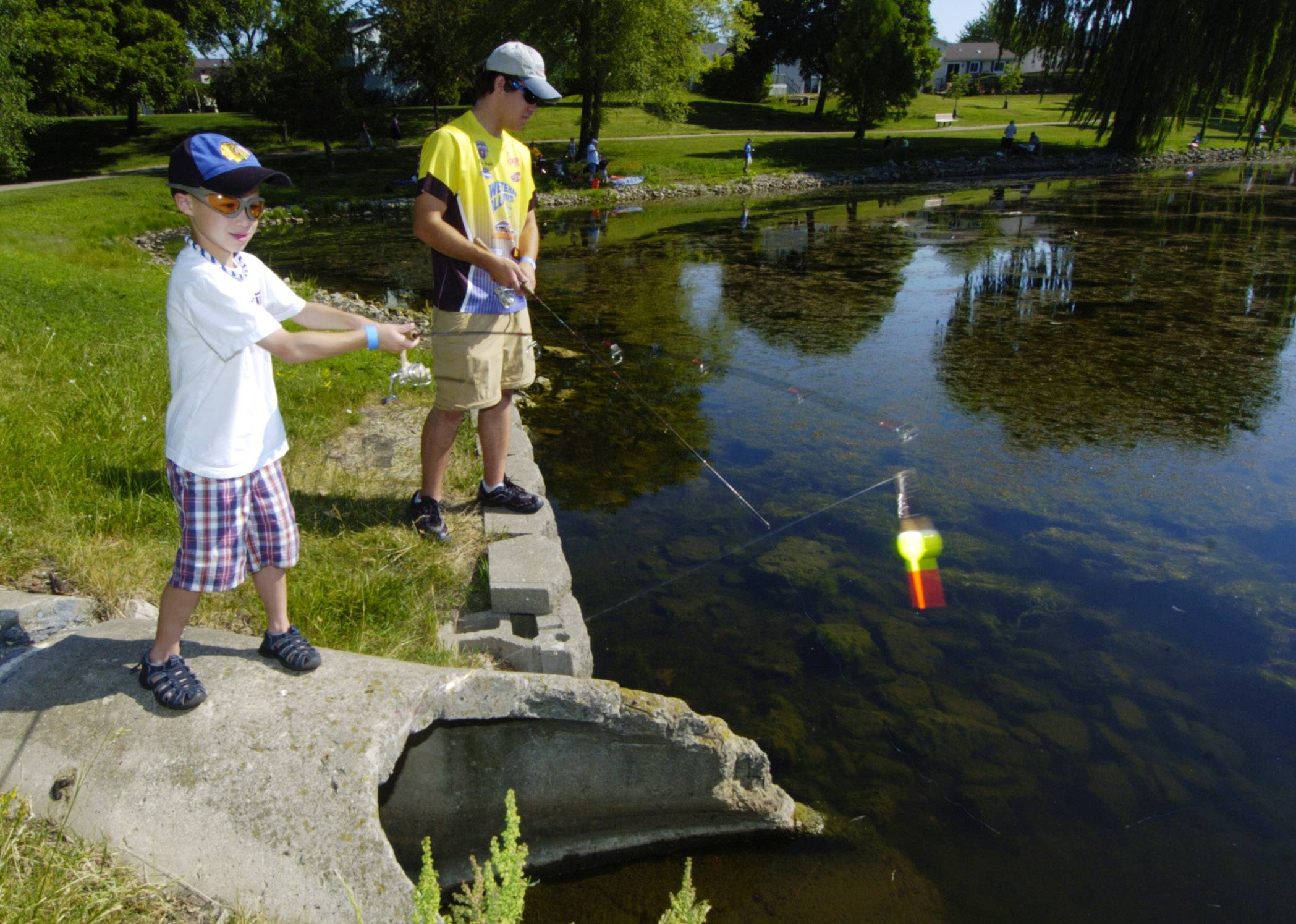 During the 2012 Community Fishing Derby at South Ridge Lake in Hoffman Estates, 7-year-old Jack Gawlik of Algonquin casts above a culvert with his cousin, Bryan Gawlik of Schaumburg.