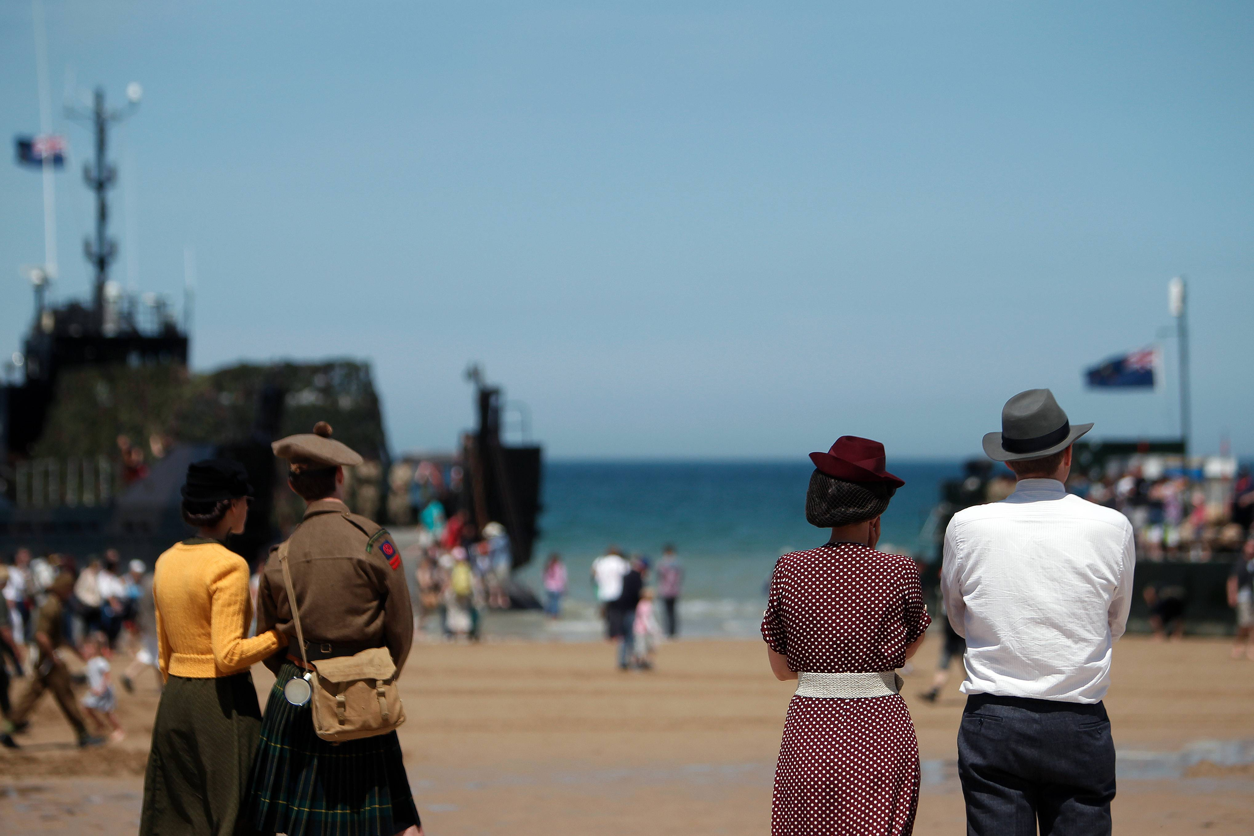 People wearing WWII style clothes look toward the sea, on the beach of Arromanches, western France, Friday June 6, 2014.
