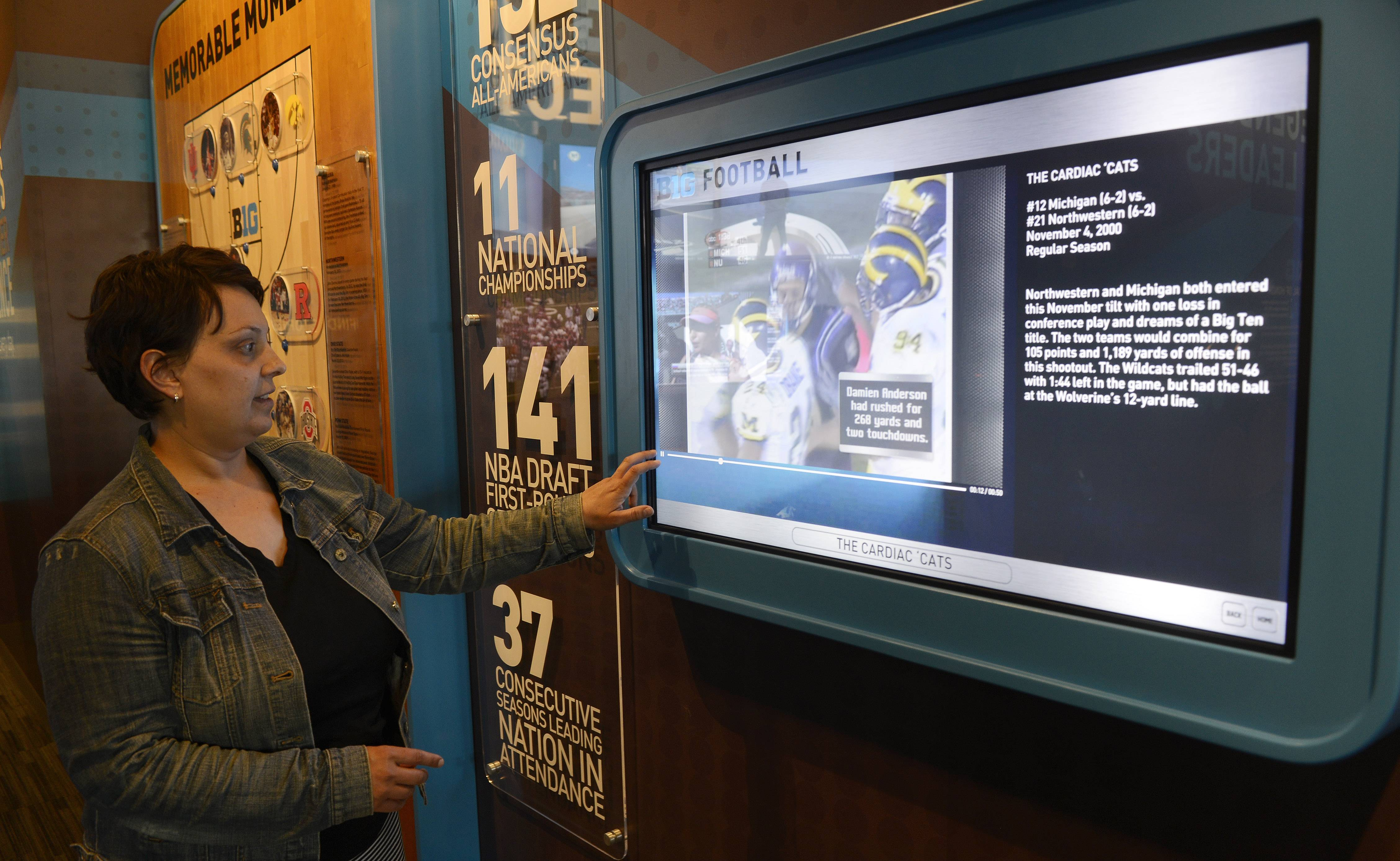 Robin Jentes, Big Ten director of branding, demonstrates the use of a display at the new Big Ten Museum, which opens Saturday in Rosemont. The museum features 13 interactive exhibits highlighting the conference's history dating back to 1896.