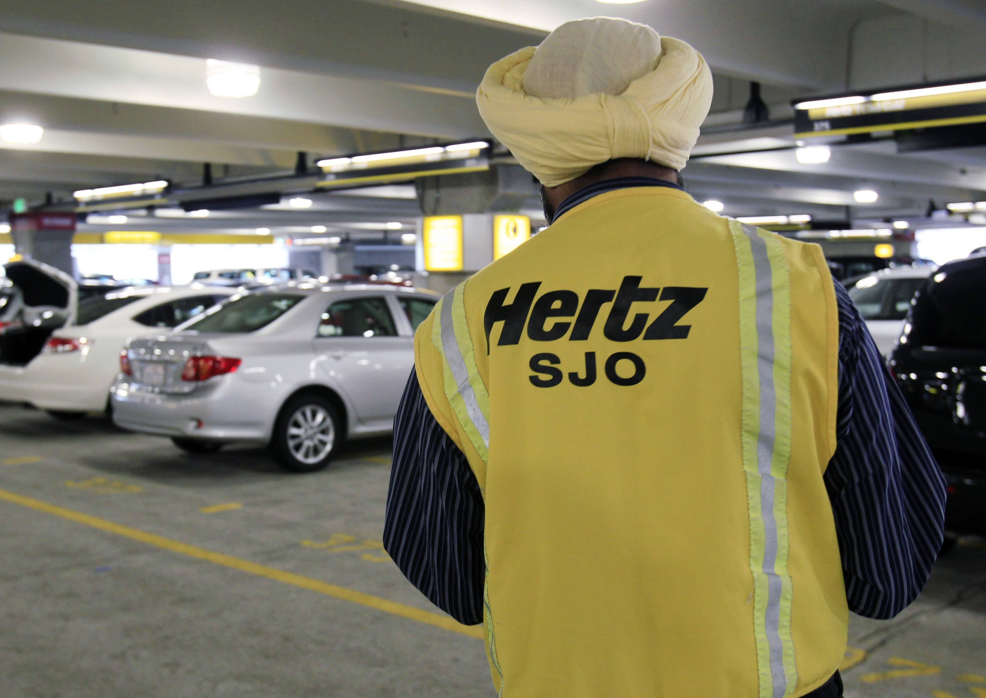 A Hertz rental car worker checks out cars at San Jose International Airport in San Jose, Calif. Hertz Global Holdings Inc. says it has to review its financial reports from the past three years after an audit by the car rental company found accounting errors.