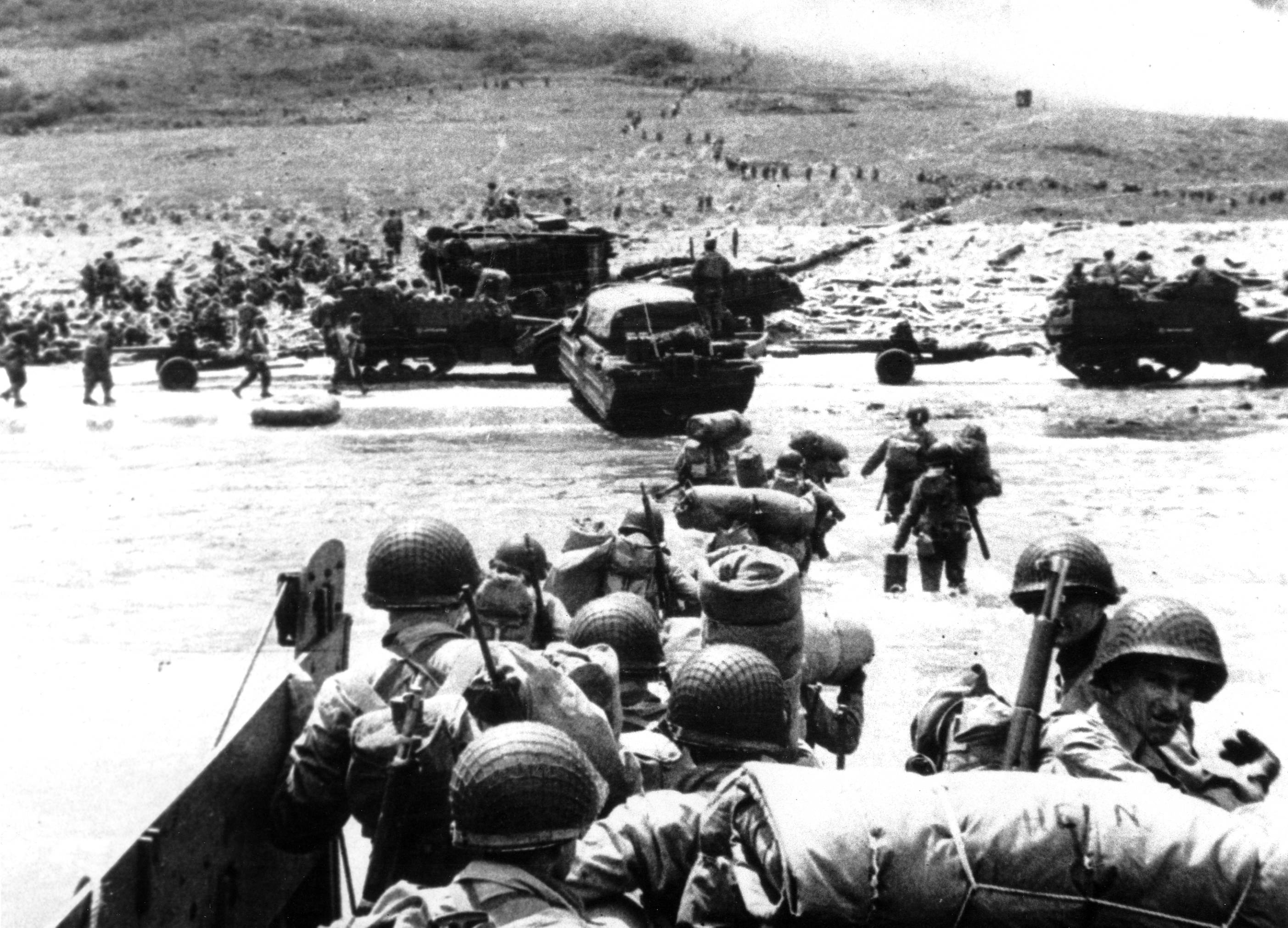 Ducks (amphibious trucks) and a half-track follow foot troops ashore during the World War II opening invasion of France on a 100-mile front along the Normandy coast by Allied forces on June 6, 1944.