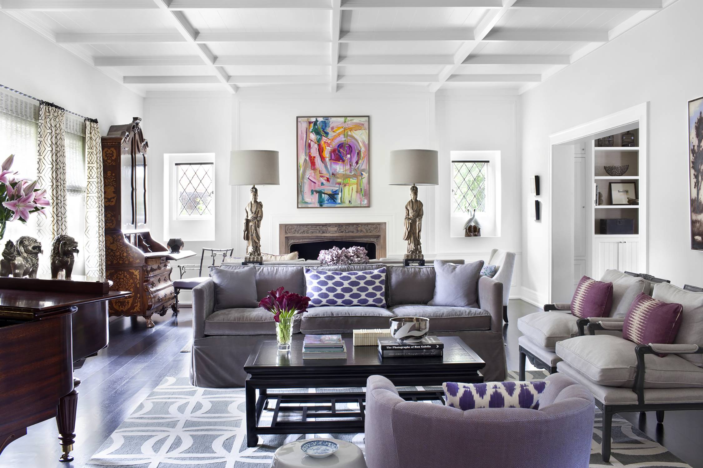 Shades of purple and lavender are mixed with softer shades of gray and black accents in a living room.
