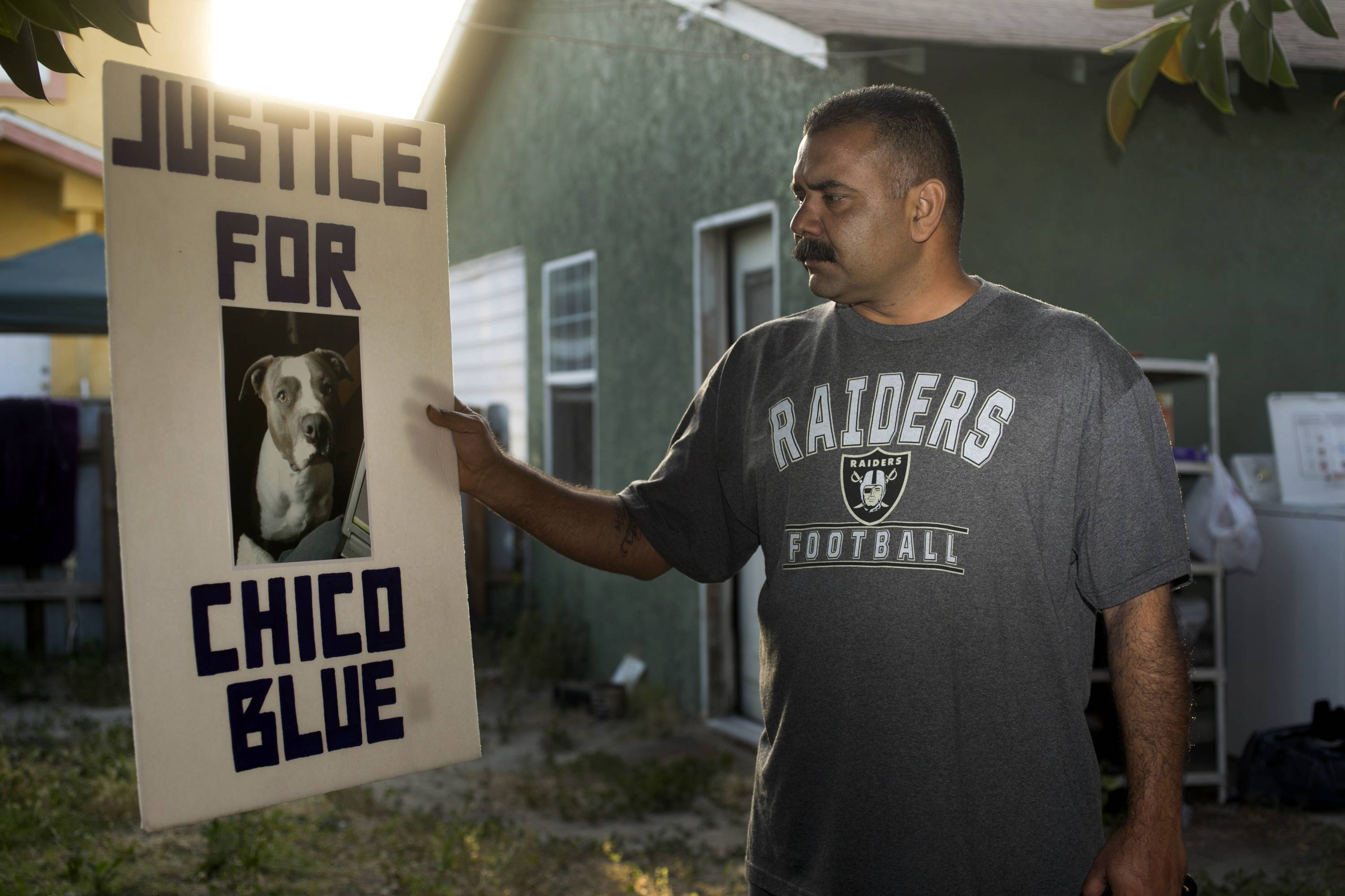 Former dog owner Arturo Gonzalez shows a photo with a picture of his late dog at his home in Pico Rivera, Calif. Gonzalez's pit bull, Chico Blue, was fatally shot by sheriff's deputies 18 months ago when the deputies came to ask Gonzalez about a shooting that wounded his brother. Feeling threatened by the dog, the deputies threw a chair, sprayed the dog with mace and shot him twice with a handgun.