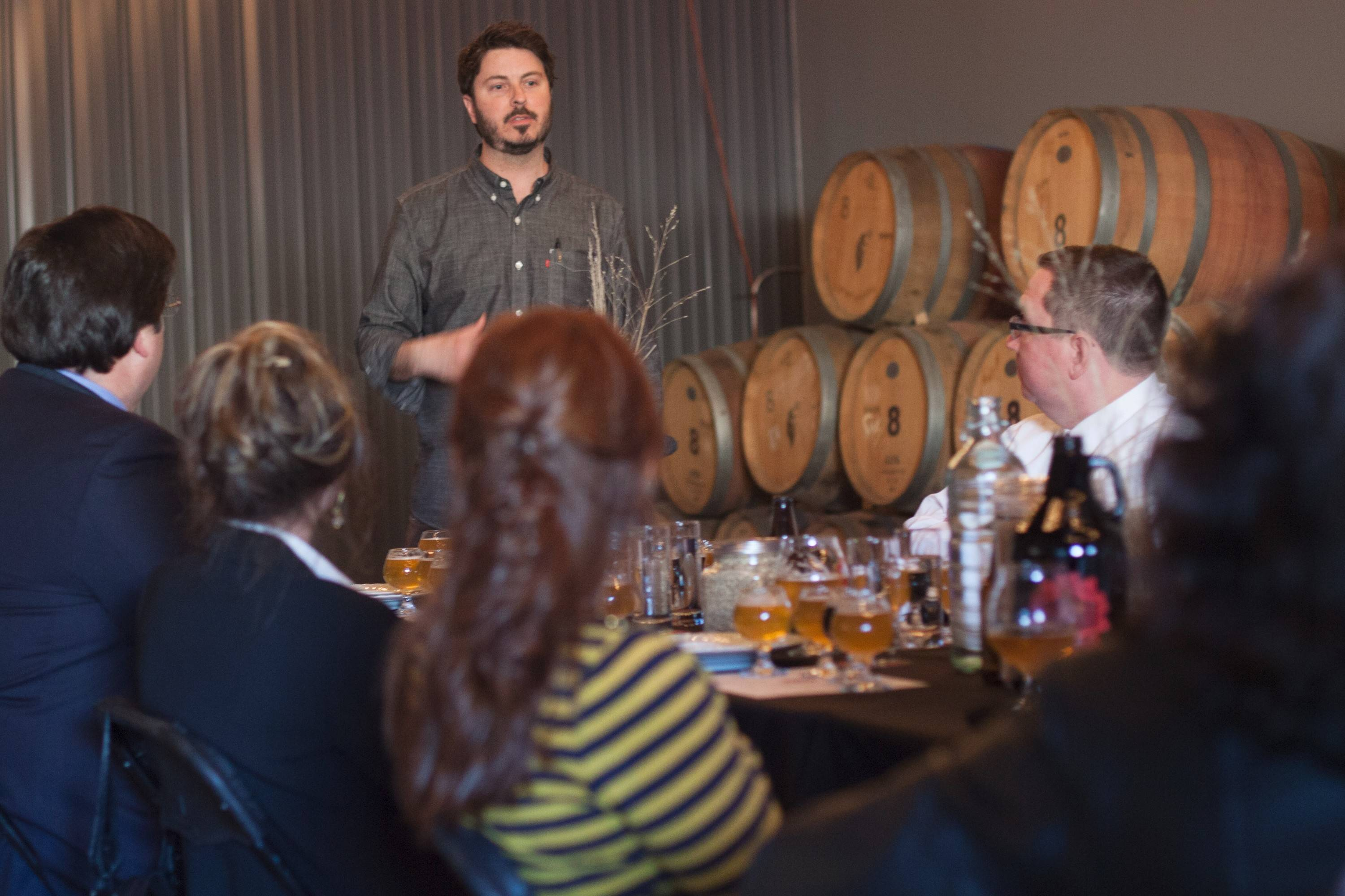 Penrose Brewing Company founder Eric Hobbs leads guests through a guided tasting of a flight of beers in the brewery's barrel cellar.