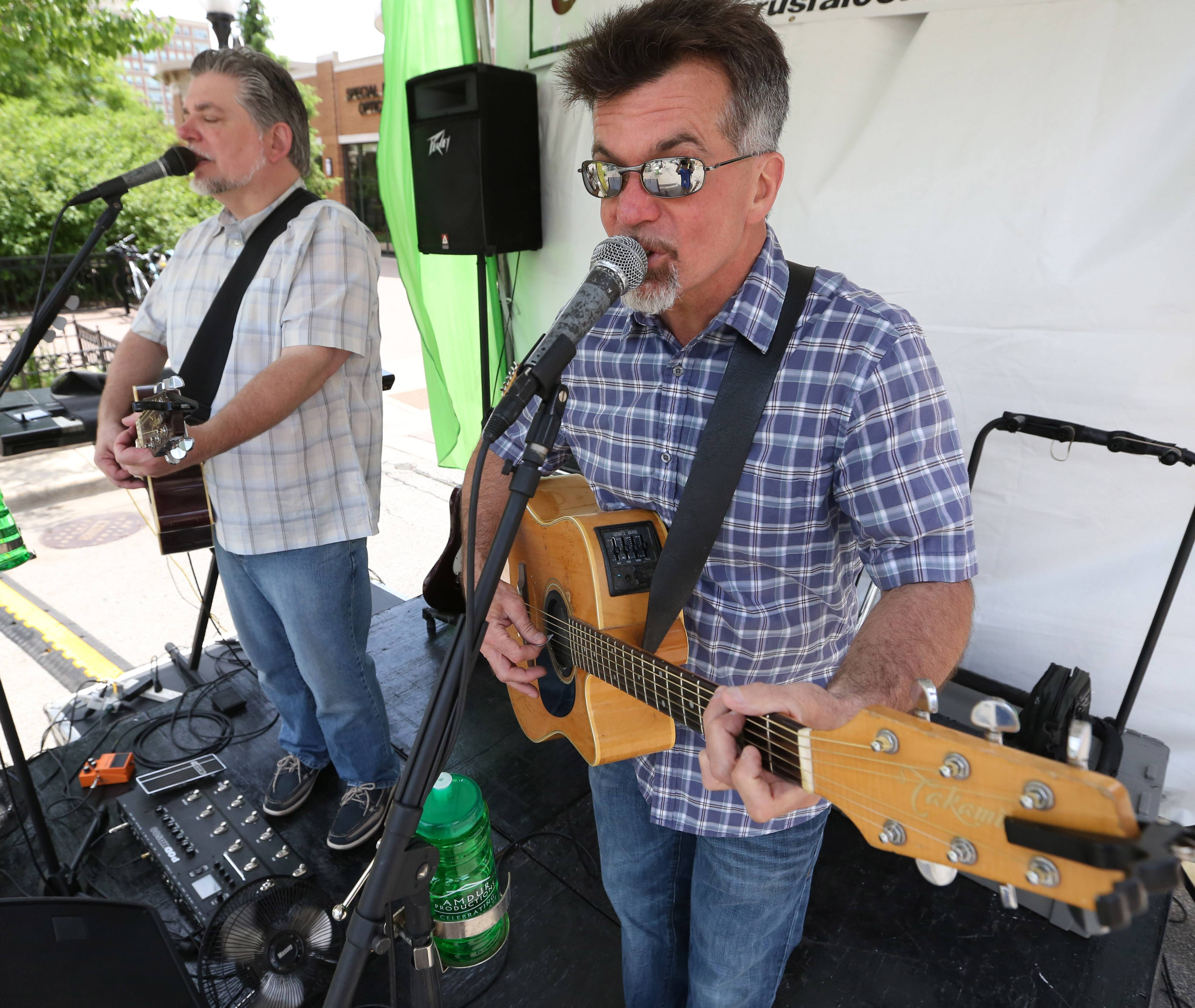 Scott Anderson, right, and Dave Granger play classic rock music at the 11th annual Promenade of Art in Arlington Heights on Saturday. The art fest features the work of 130 juried artists.