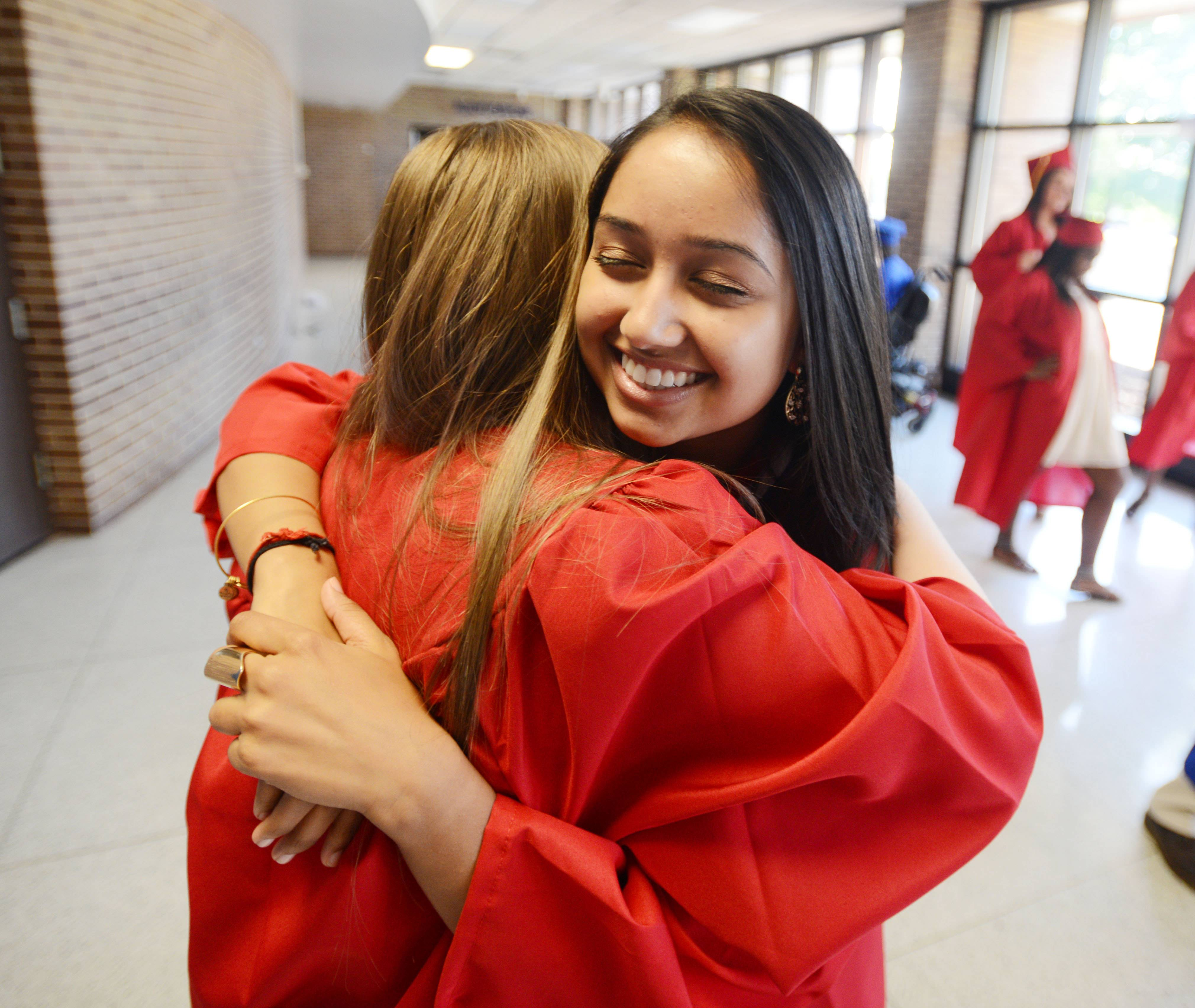 Jennifer Lipa,17, of Glen Ellyn hugs Nisha Choksi,18, of Wheaton during the Glenbard South High School Graduation Friday.