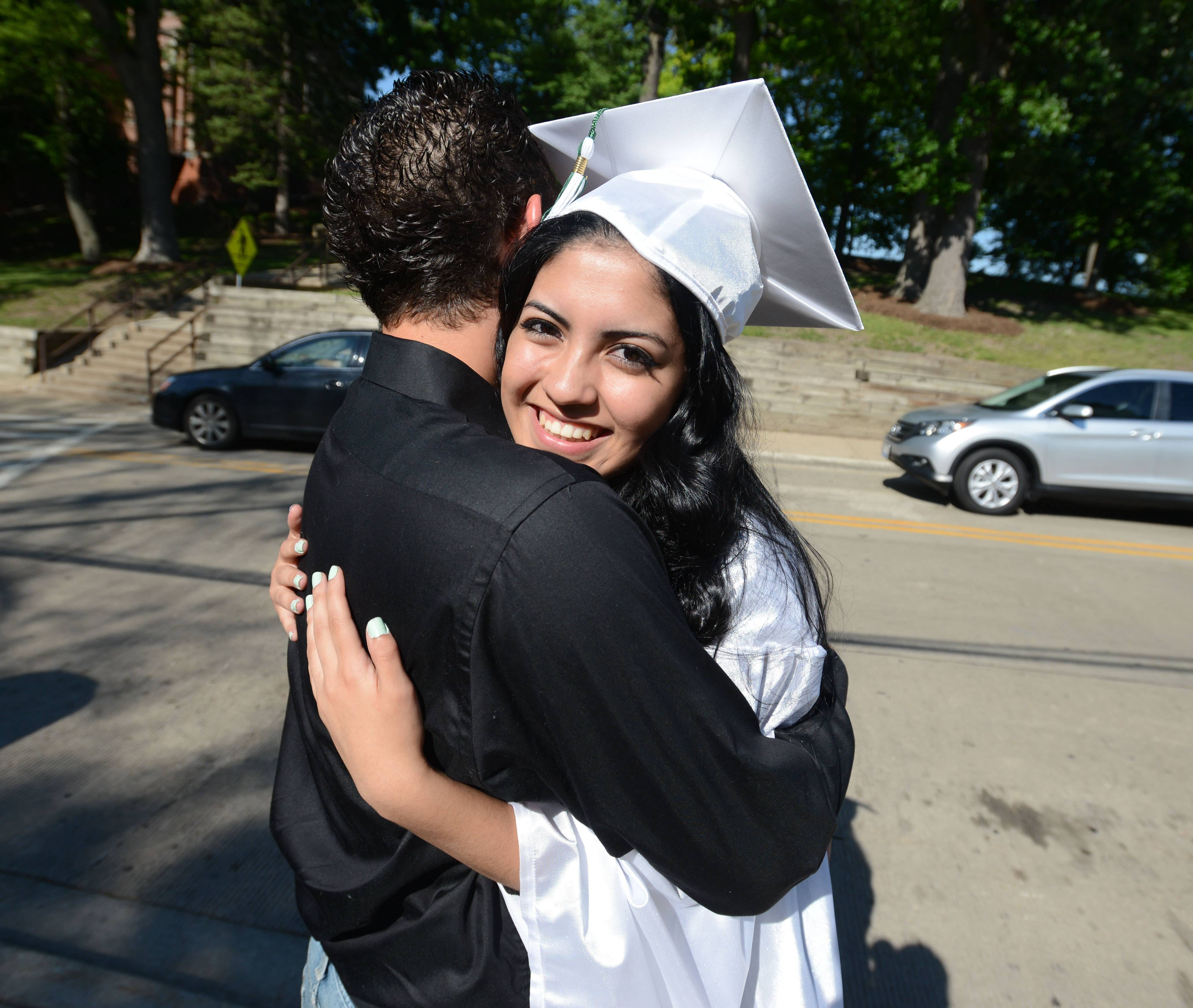 Carlos Robles,18, of Carol Stream hugs Ana Ramirez,18, of Glendale Heights before the Glenbard West High School graduation ceremony Friday.