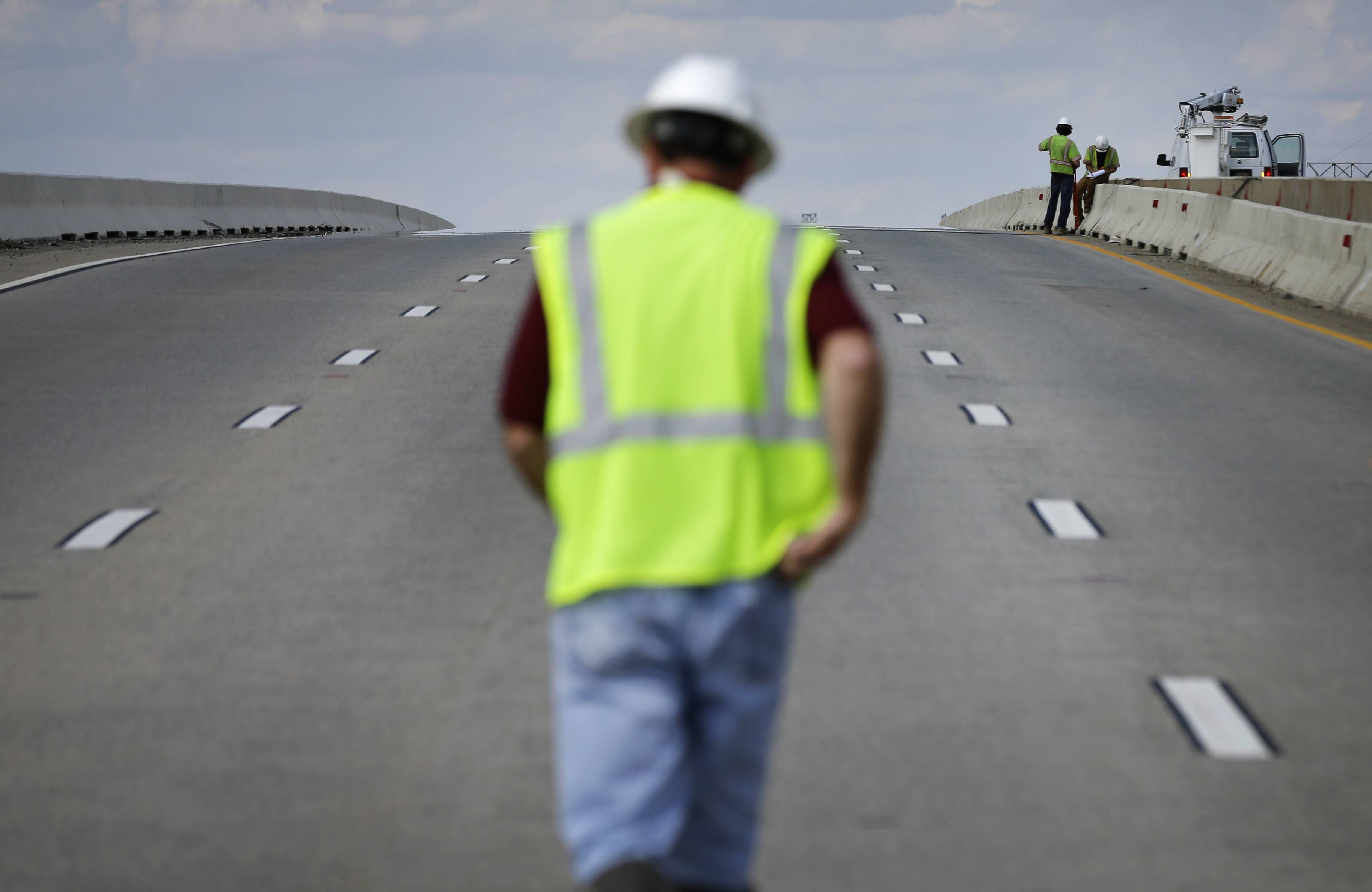 An official walks Thursday toward a wall, right, separating the north and southbound lanes of the Interstate 495 bridge over the Christina River near Wilmington, Del.