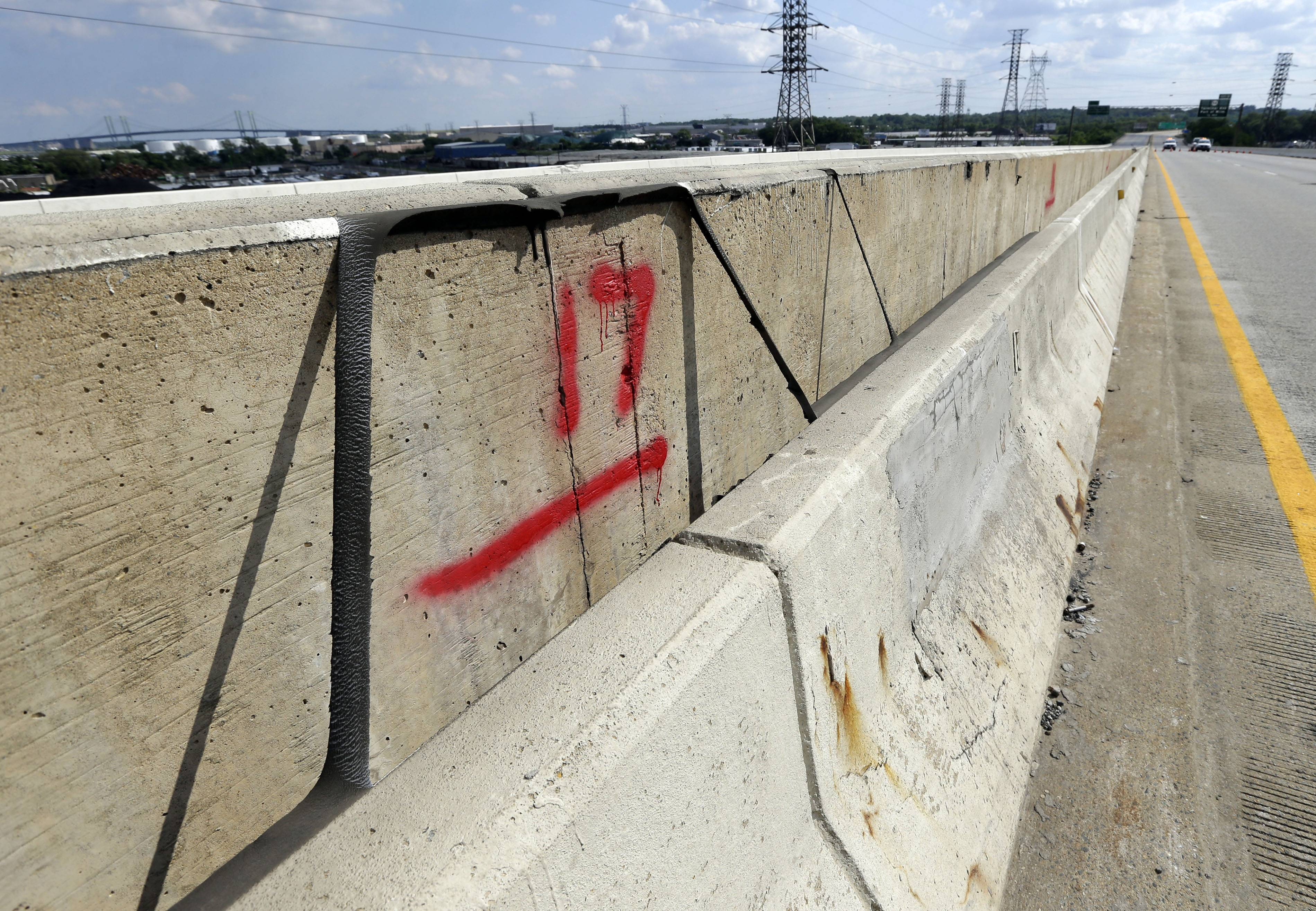 Spray paint shows a 17-inch difference between the tops of walls separating the north and southbound lanes of the Interstate 495 bridge over the Christina River near Wilmington, Del.