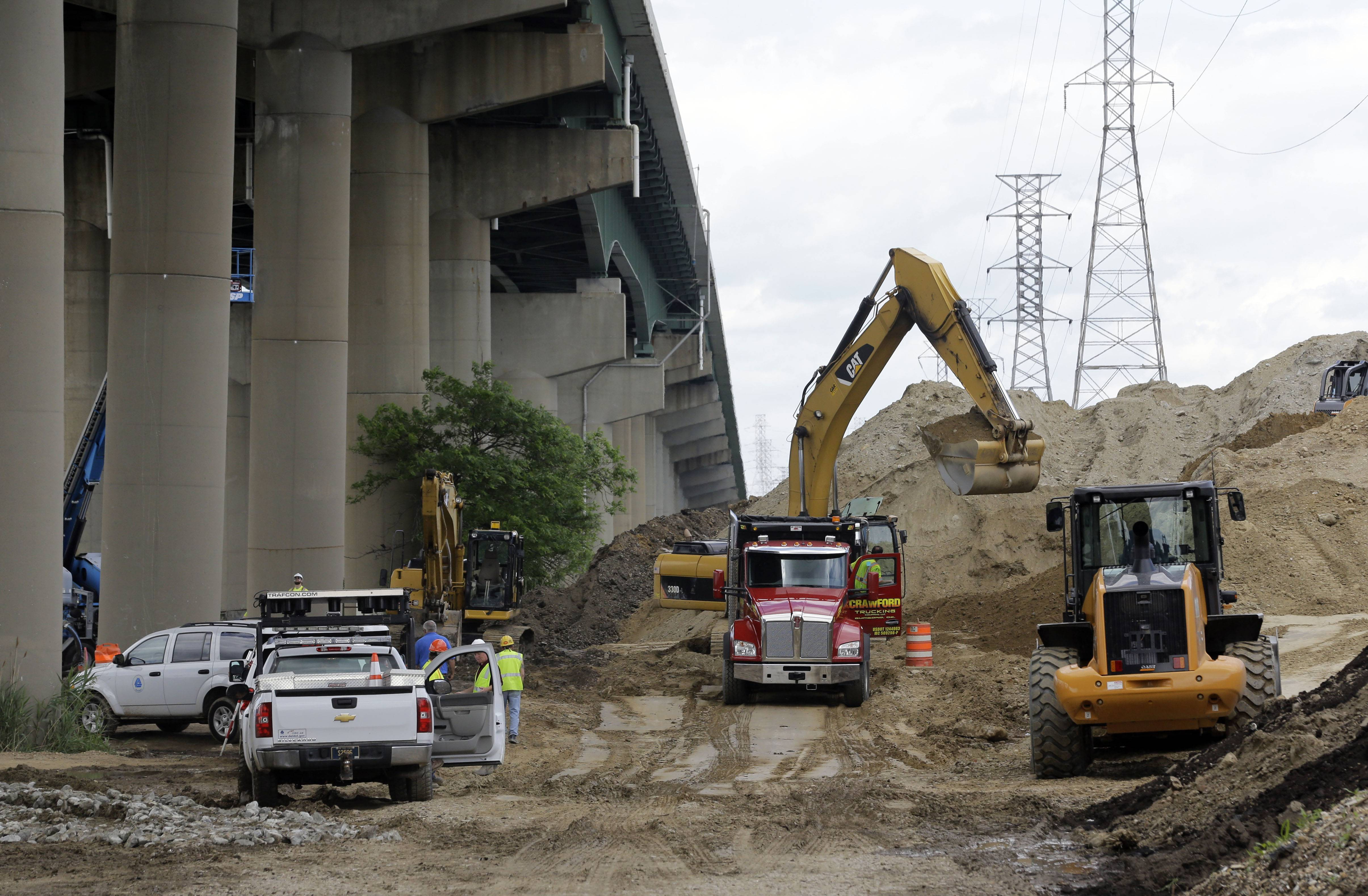 Workers remove a pile of dirt Thursday next to the Interstate 495 bridge over the Christina River.