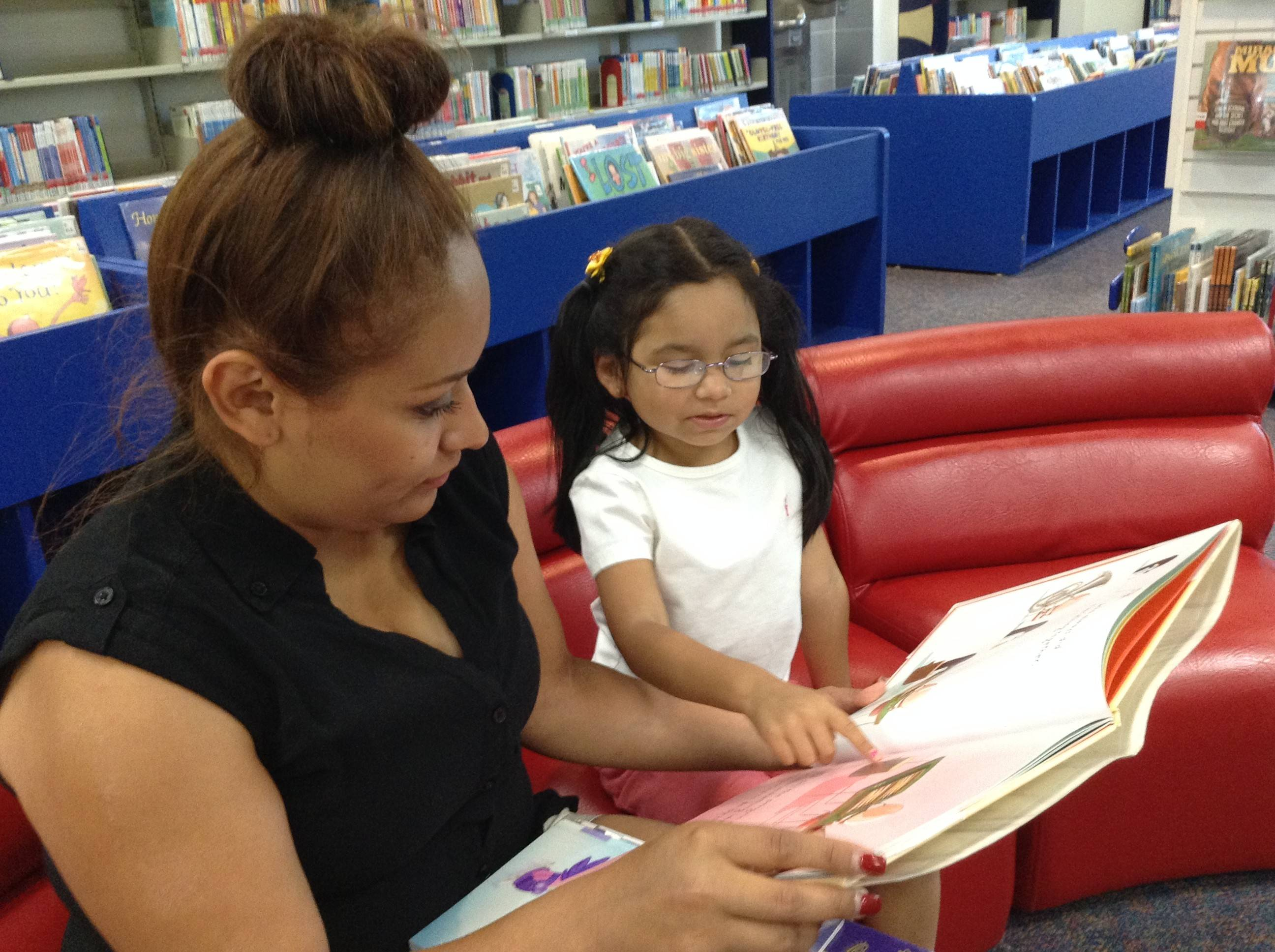 Brenda Hurtado reads with her 5-year-old daughter, Deevani, at the Fremont Public Library in Mundelein. The library is launching a program to encourage young children to read.