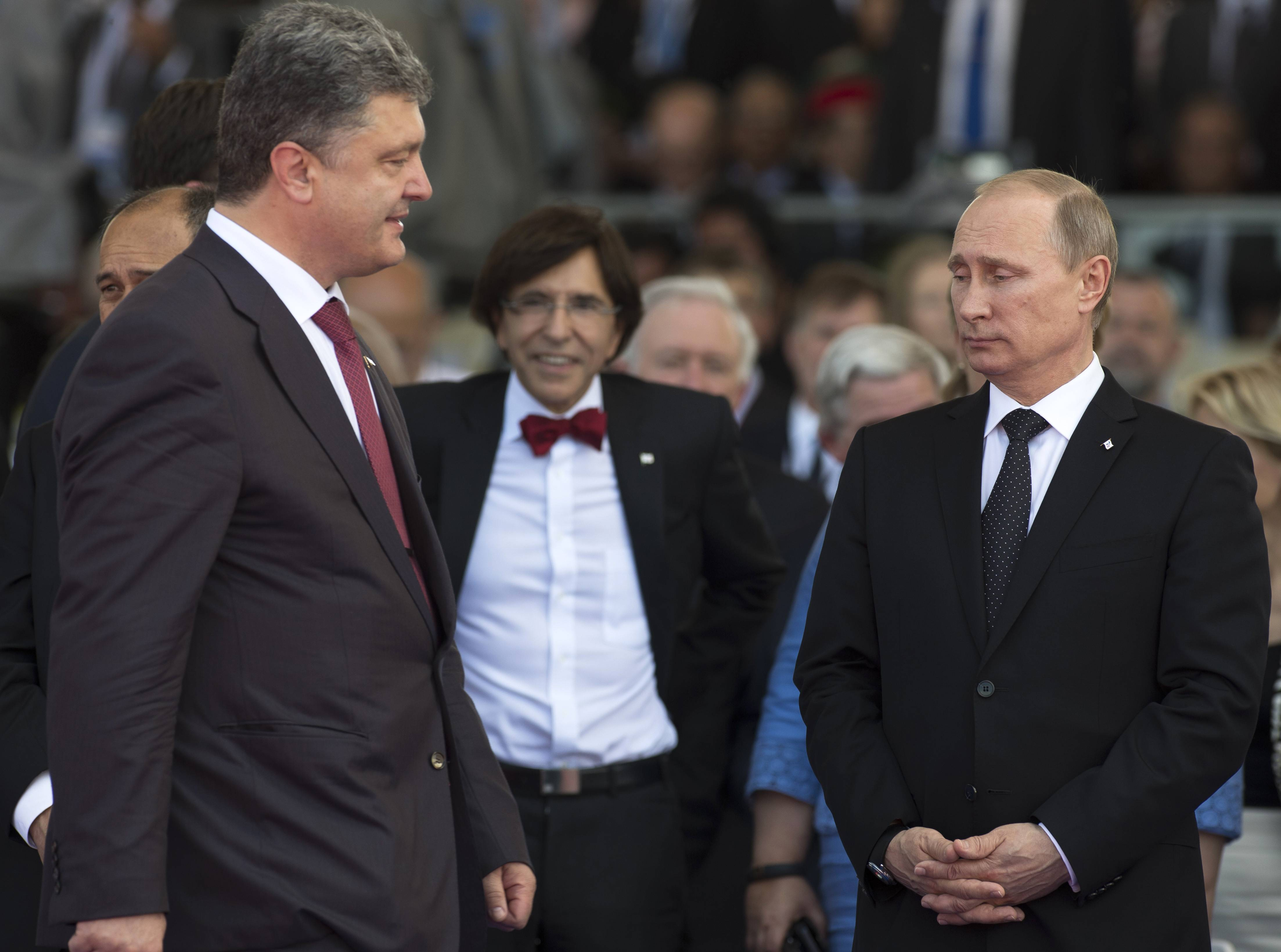 Ukraine's President-elect Petro Poroshenko, left, walks past Russian President Vladimir Putin, right, during the commemoration of the 70th anniversary of the D-Day in Ouistreham, western France, Friday, June 6, 2014.