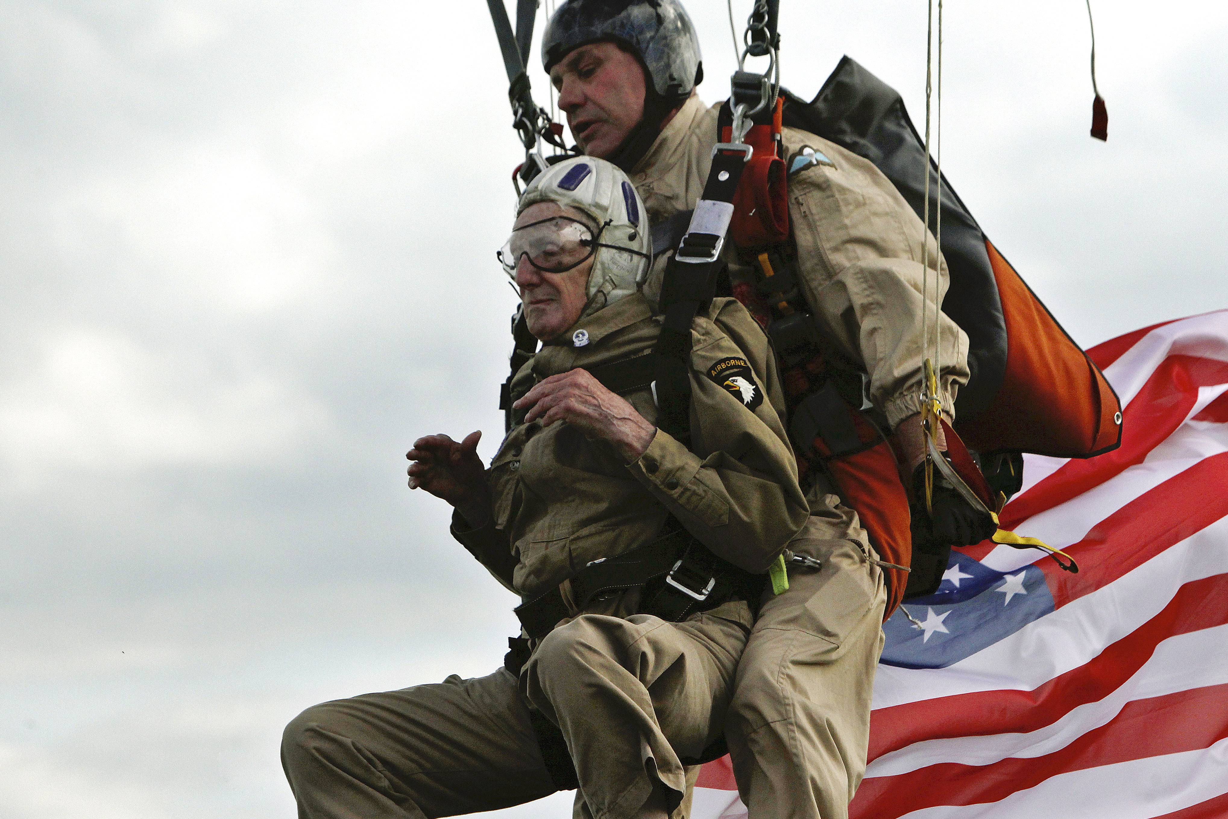 93-year-old U.S. WW II veteran Jim Martin of the 101st Airborne, left, completes a tandem parachute jump onto Utah Beach, western France, Thursday June 5, 2014, as part of the commemoration of the 70th anniversary of the D Day.