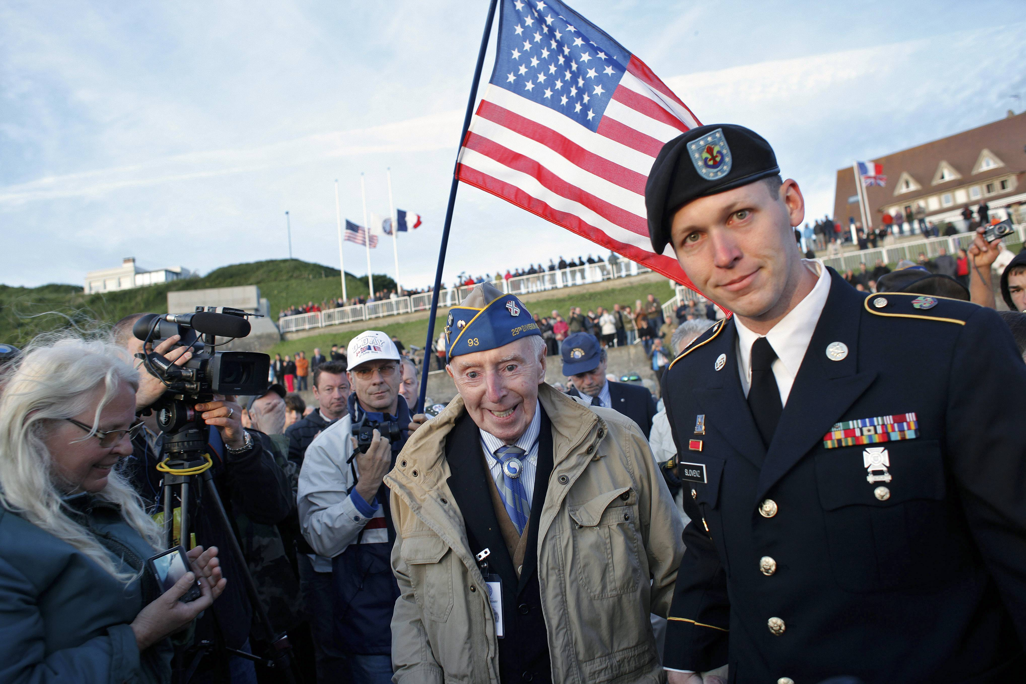 World War II veteran of the U.S. Army 29th Infantry Division, Don McCarthy, 90, from Maryland, center, arrives for a D-Day commemoration, on Omaha Beach, western France, Friday June 6, 2014.