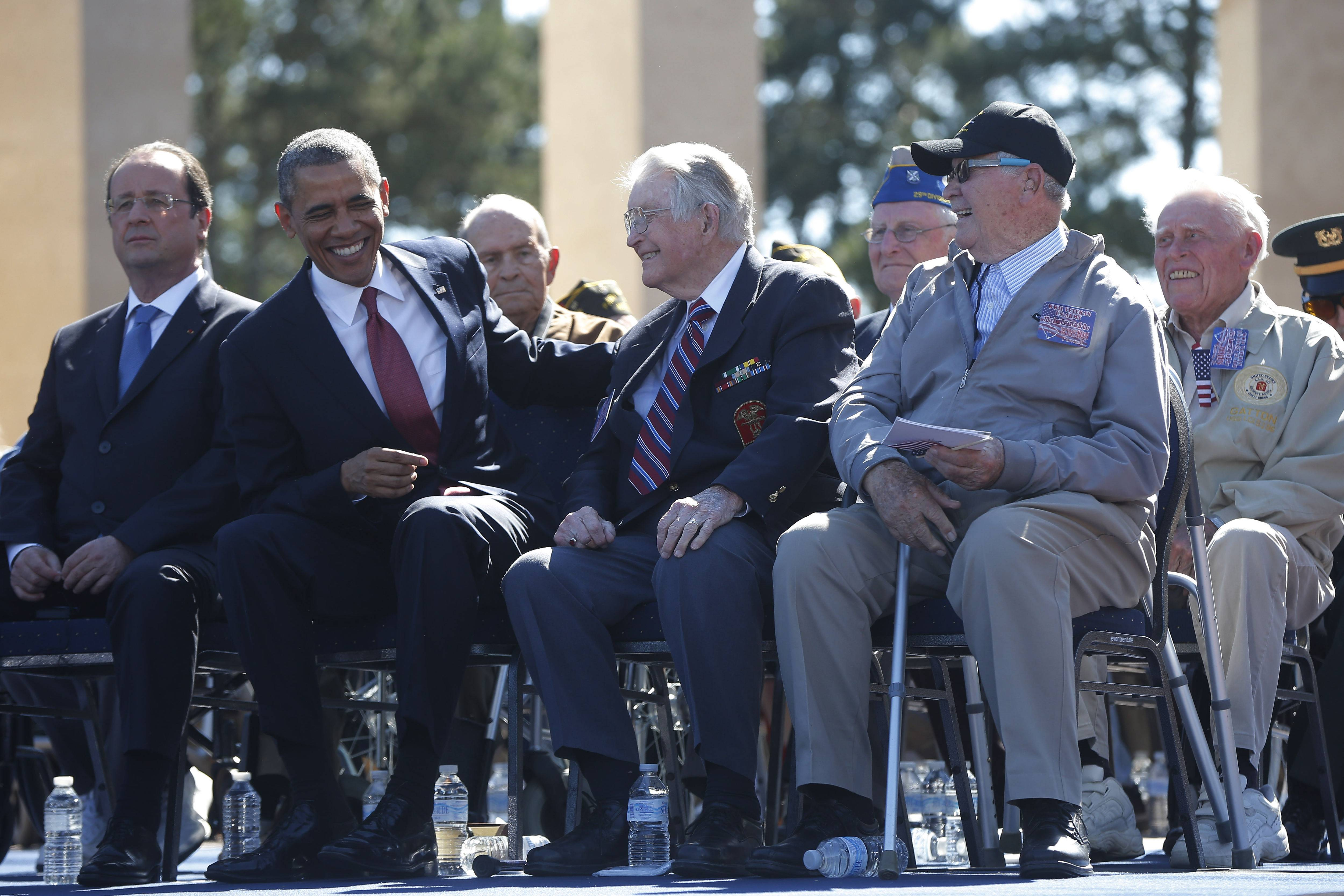 President Barack Obama and French President Francois Hollande sit onstage with veterans, at Normandy American Cemetery at Omaha Beach as he participates in the 70th anniversary of D-Day.