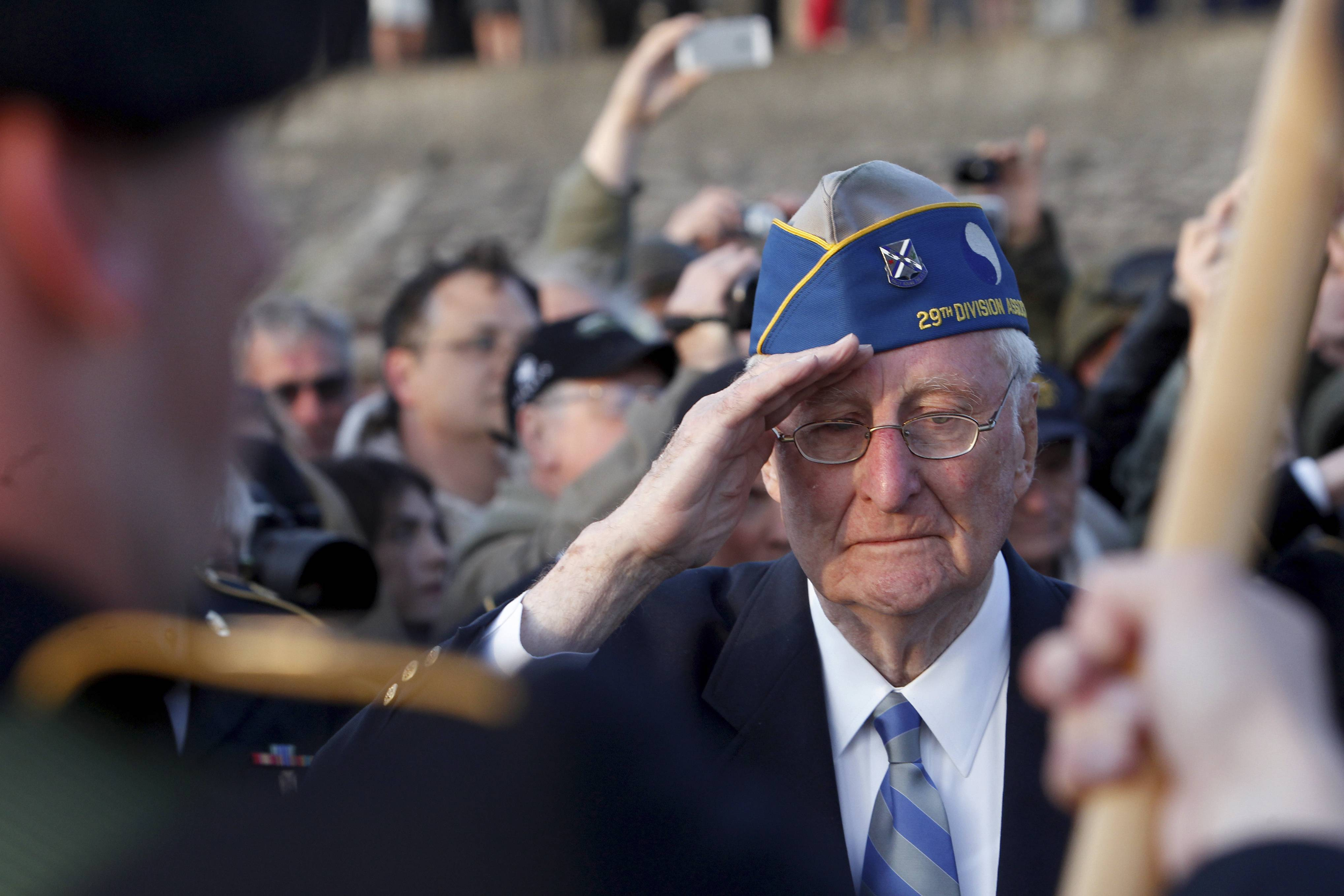 World War II veteran of the U.S. 29th Infantry Division, Morley Piper, 90, Mass., salutes during a D-Day commemoration, on Omaha Beach in Vierville Sur Mer, western France, Friday June 6, 2014.