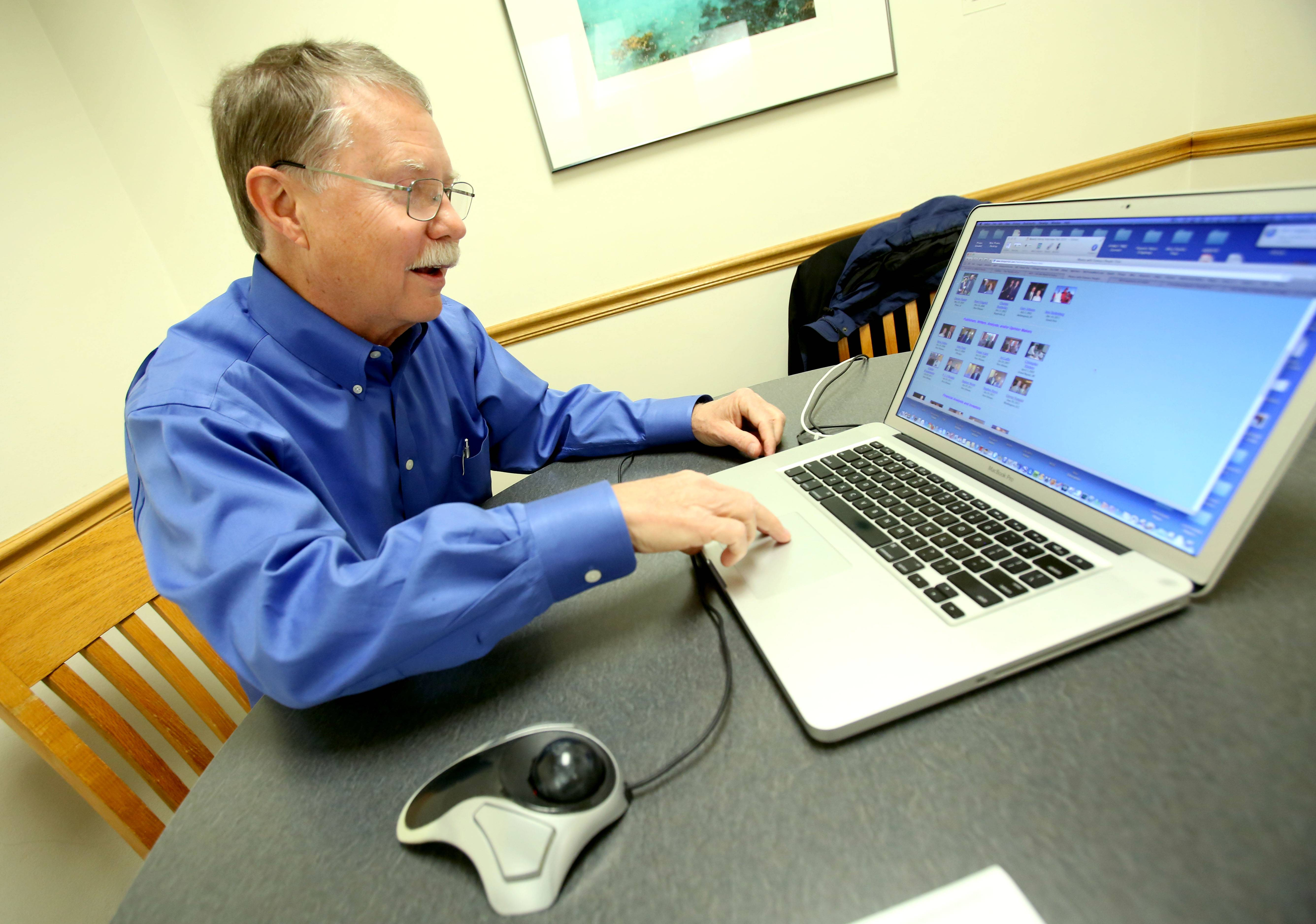 Don Parrish looks over some photos on his laptop. He doesn't collect souvenirs when he travels, but has around 80,000 photos.