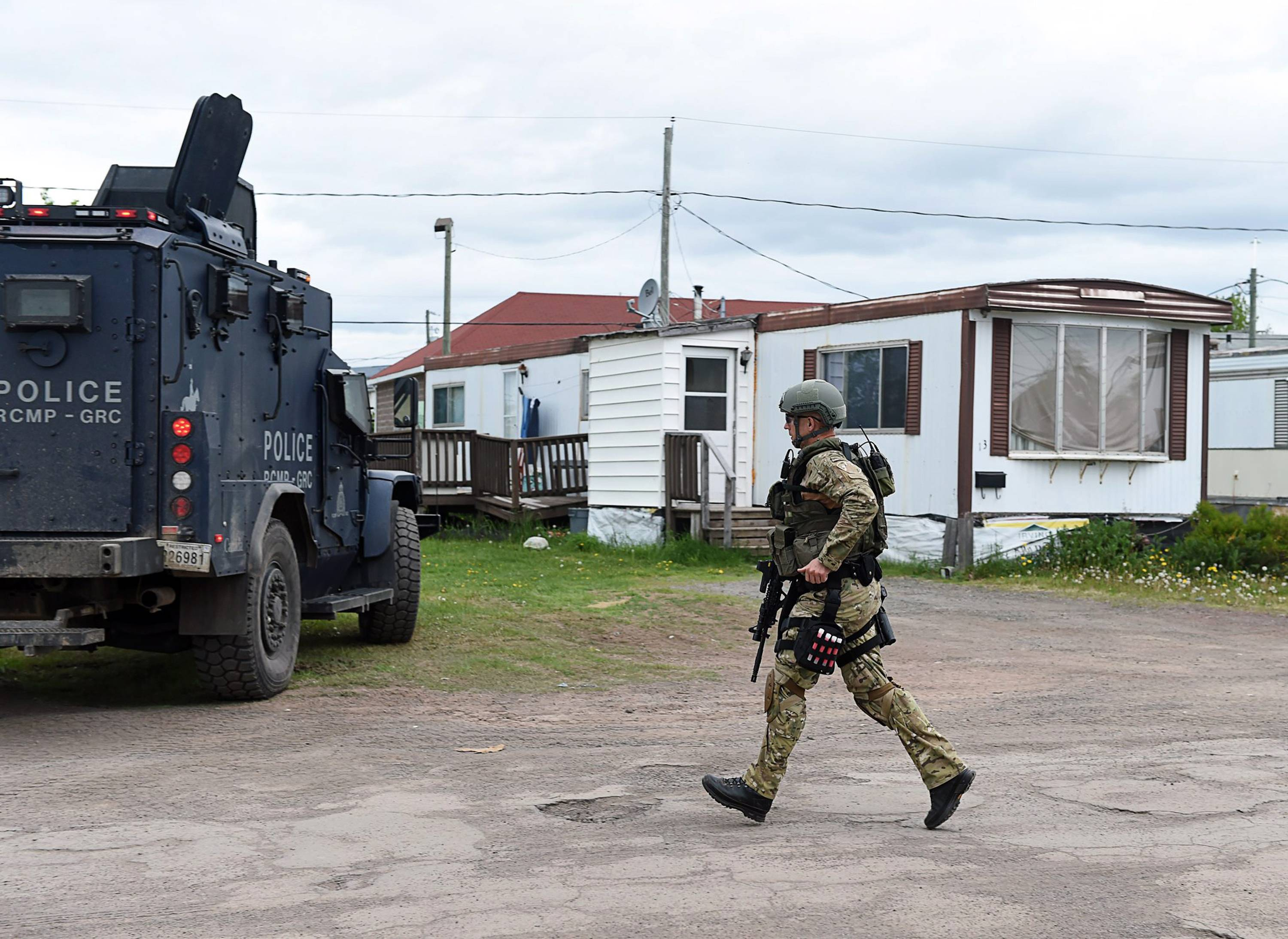 An emergency response team member runs past a trailer where murder suspect 24-year-old Justin Bourque resides in Moncton, New Brunswick, on Thursday.