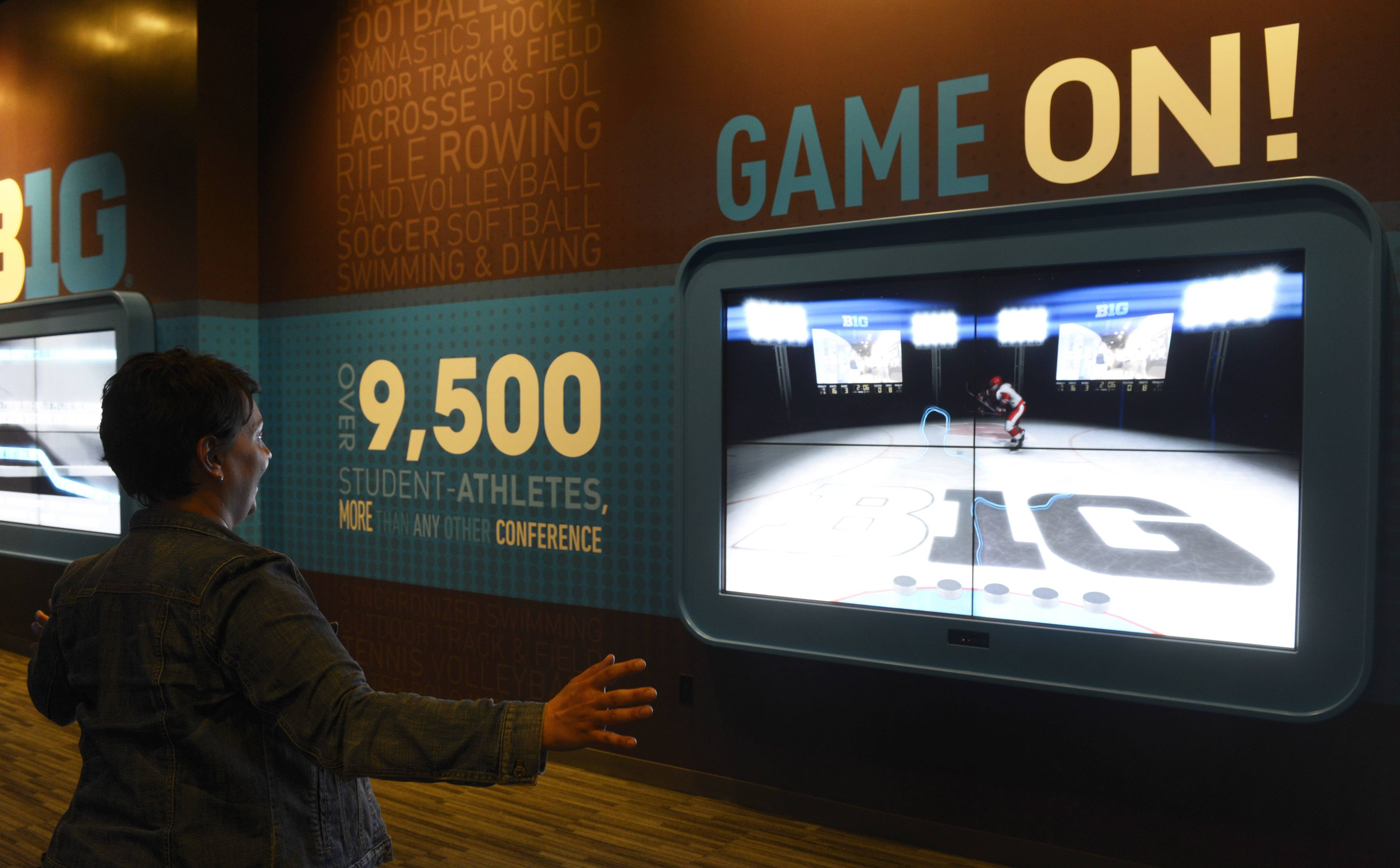 Robin Jentes, Big Ten director of branding, tries her skills as a hockey goalie while using a display at the new Big Ten Museum, which opens Saturday in Rosemont.