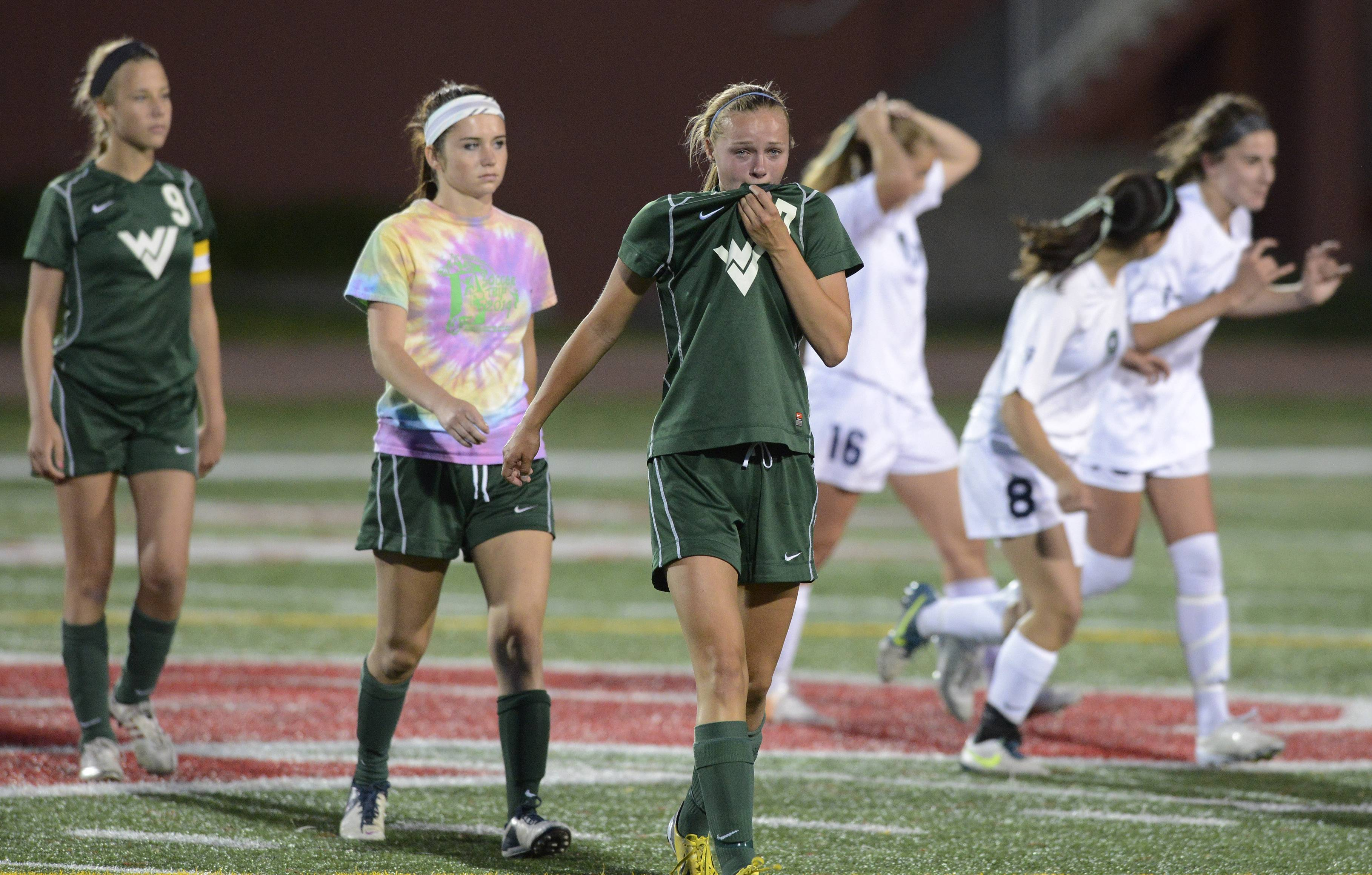 Maddie Pokora, middle, walks off the field with her teammates as New Trier celebrates its 1-0 win during the girls soccer Class 3A state semifinal at North Central College in Naperville Friday.