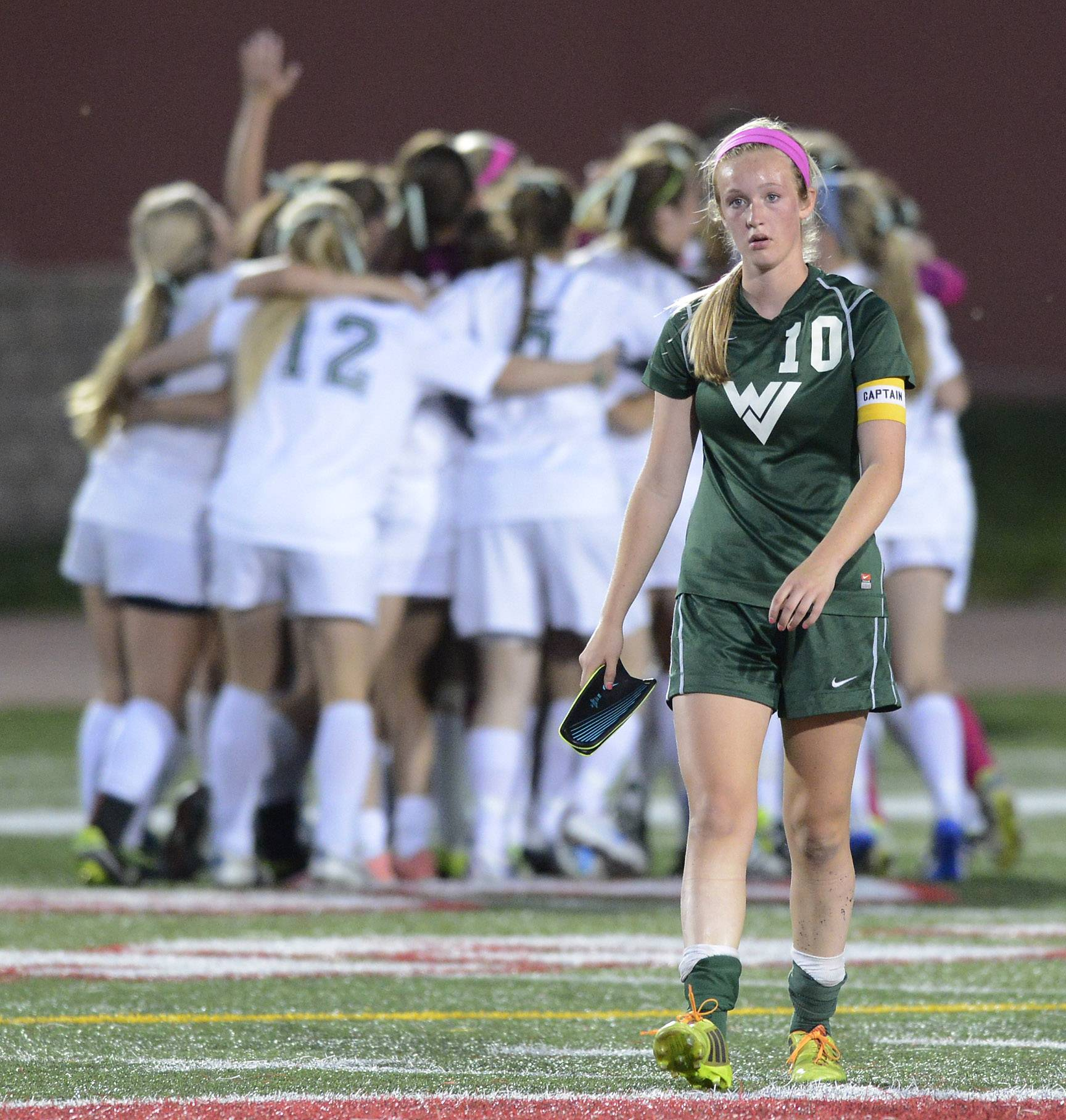 Waubonsie Valley's Mackenzie Fuller walks off the field as New Trier players celebrate their 1-0 win during the girls soccer Class 3A state semifinal at North Central College in Naperville Friday.