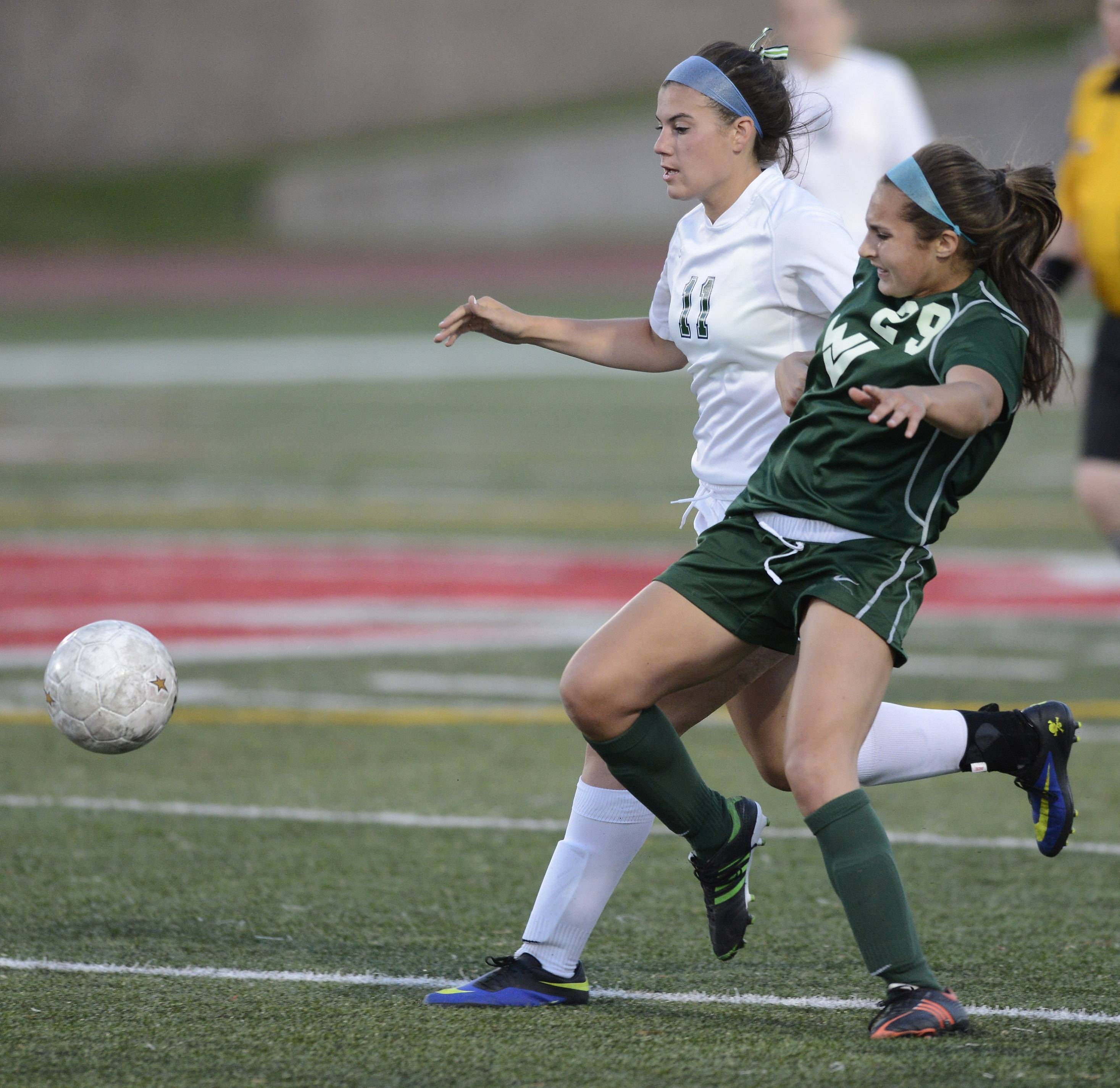 New Trier's Alex Bukovac, left, and Waubonsie Valley's Callie Vitro pursue the ball during the girls soccer Class 3A state semifinal at North Central College in Naperville Friday.