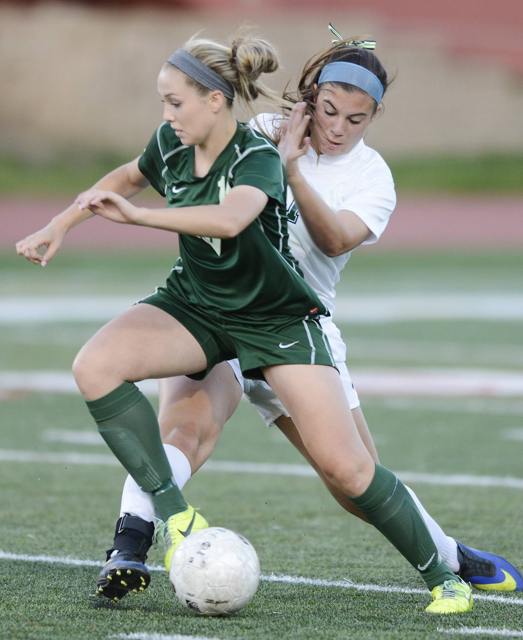 Waubosnie Valley's Maggie Roe, left, and New Trier's Alex Bukovac make contact as they pursue the ball during the girls soccer Class 3A state semifinal at North Central College in Naperville Friday.