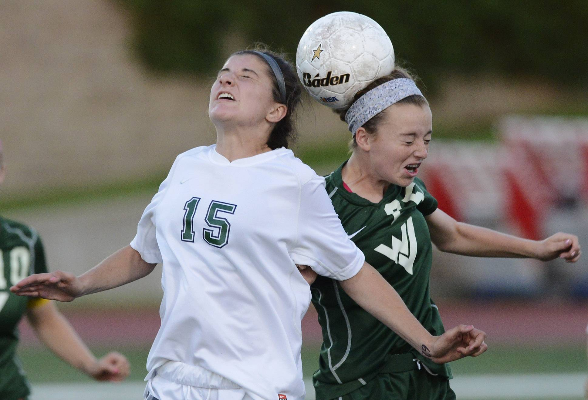 New Trier's Celia Frei, left, and Waubonsie Vallye's Sarah Griffith leap for a header during the girls soccer Class 3A state semifinal at North Central College in Naperville Friday.