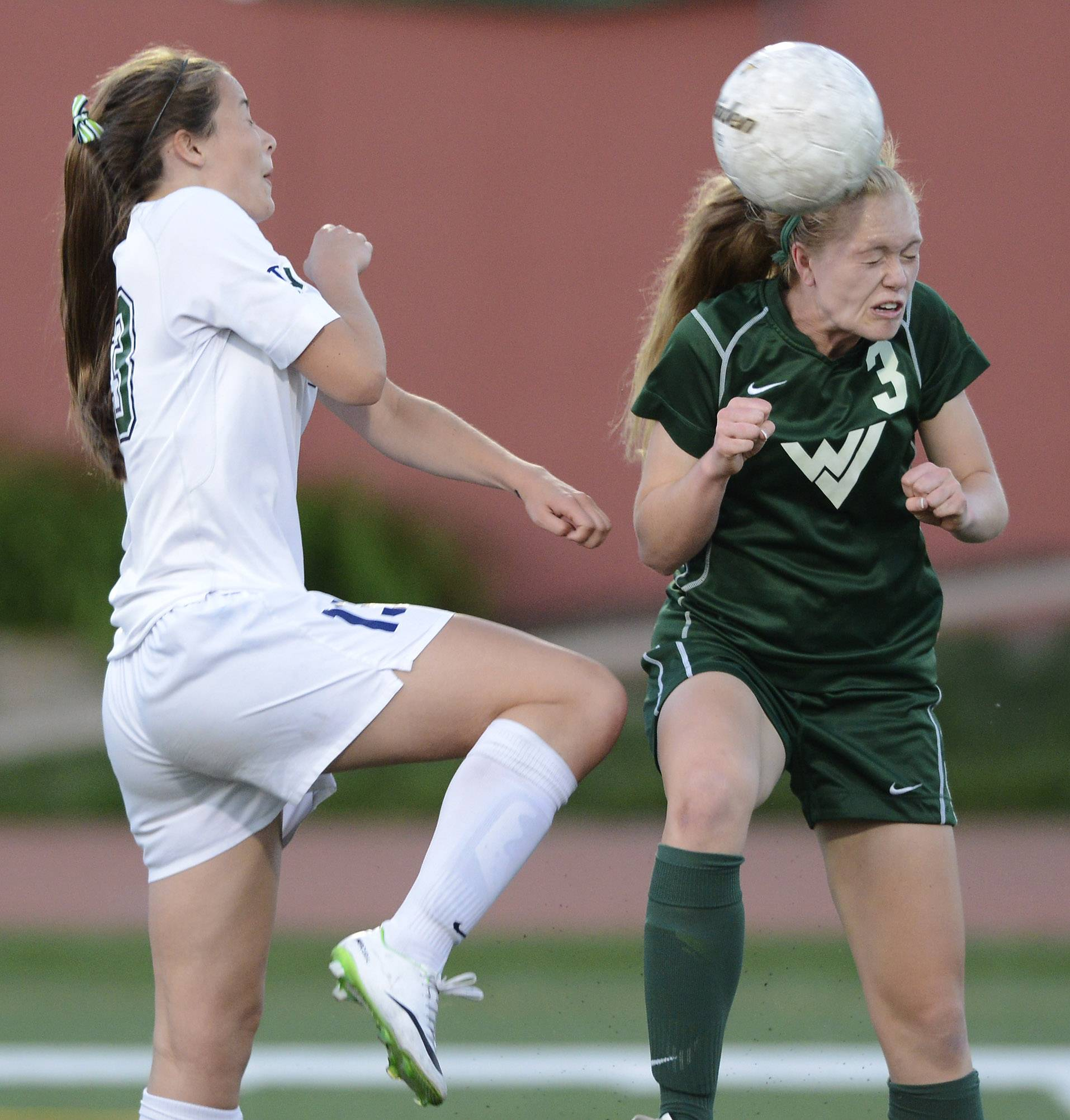 Waubonsie Valley's Morgan Kemerling, right, directs the ball with a header in front of New Trier's Jackie Welch during the girls soccer Class 3A state semifinal at North Central College in Naperville Friday.