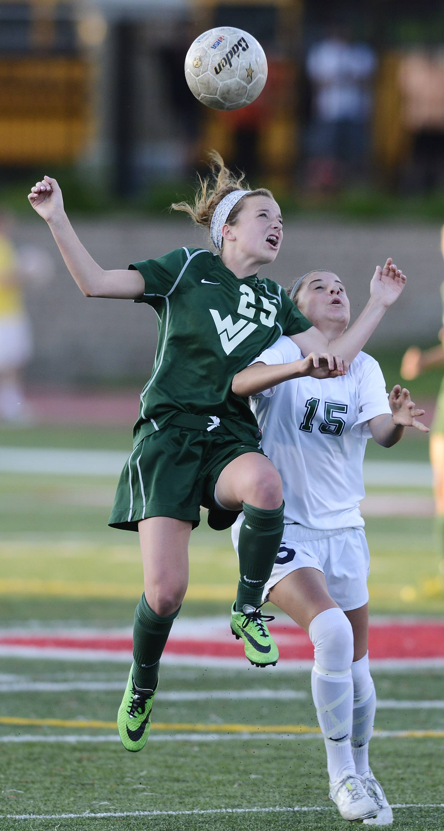 Sarah Griffith, left, of Waubonsie Valley, and Celia Frei of New Trier leap for a header during the girls soccer Class 3A state semifinal at North Central College in Naperville Friday.