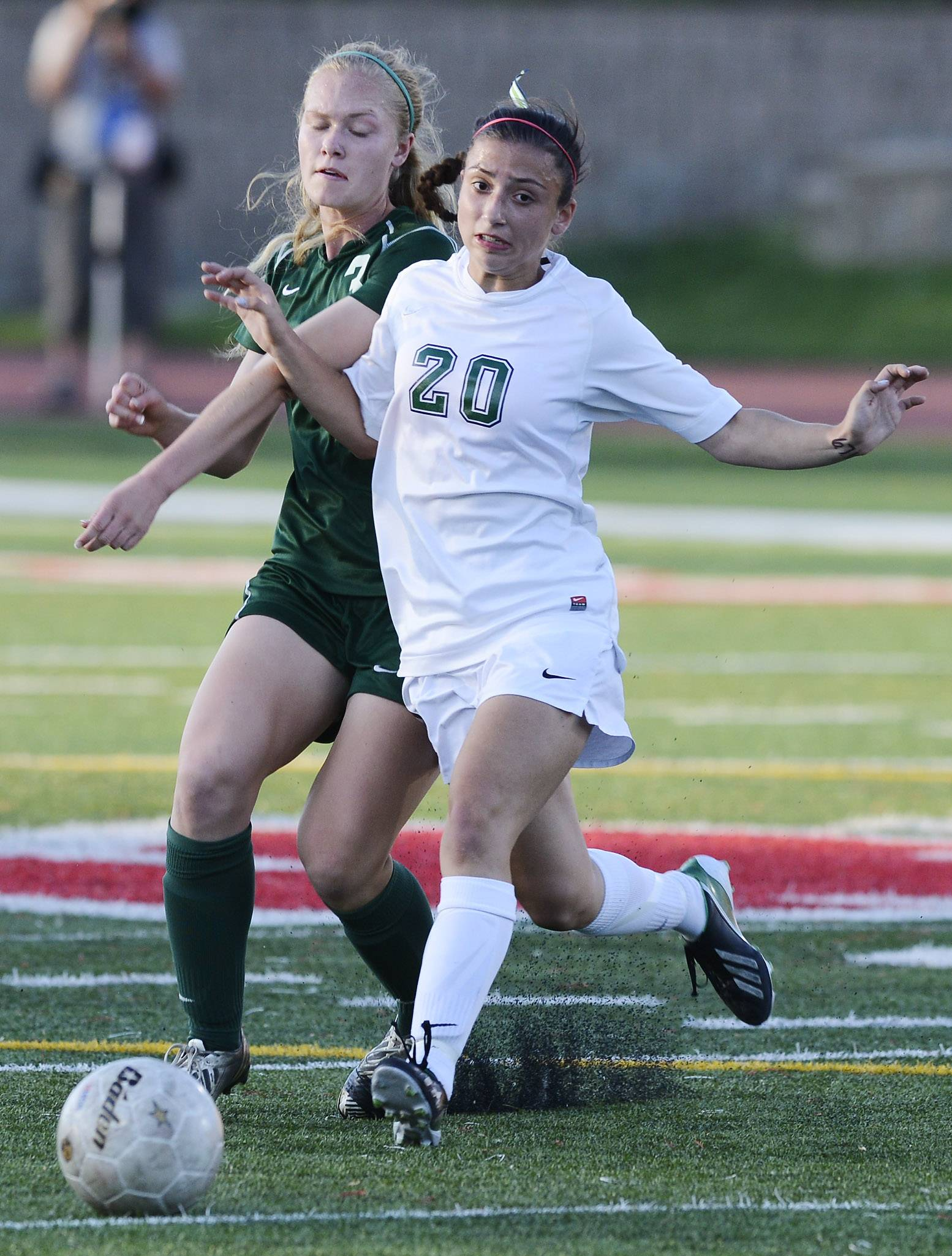 Waubonsie Valley's Morgan Kemerling, left, and New Trier's Bina Saipi make contact as they pursue the ball  during the girls soccer Class 3A state semifinal against at North Central College in Naperville Friday.