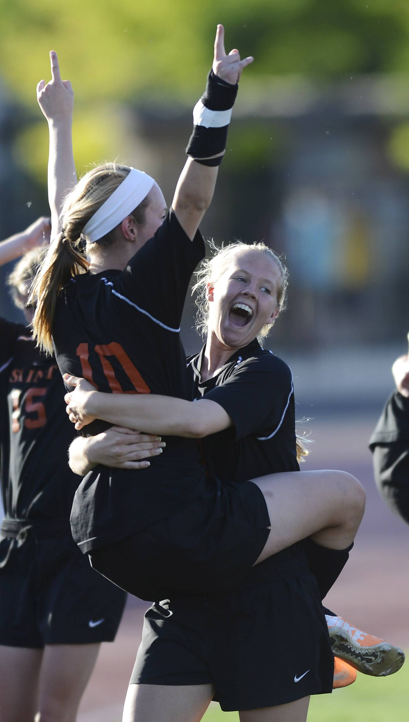 Laura Olney, right, of St. Charles East carries teammate Clair Rasmussen as they celebrate their 3-1 victory over Lincoln Way North during the girls soccer Class 3A state semifinal at North Central College in Naperville Friday.