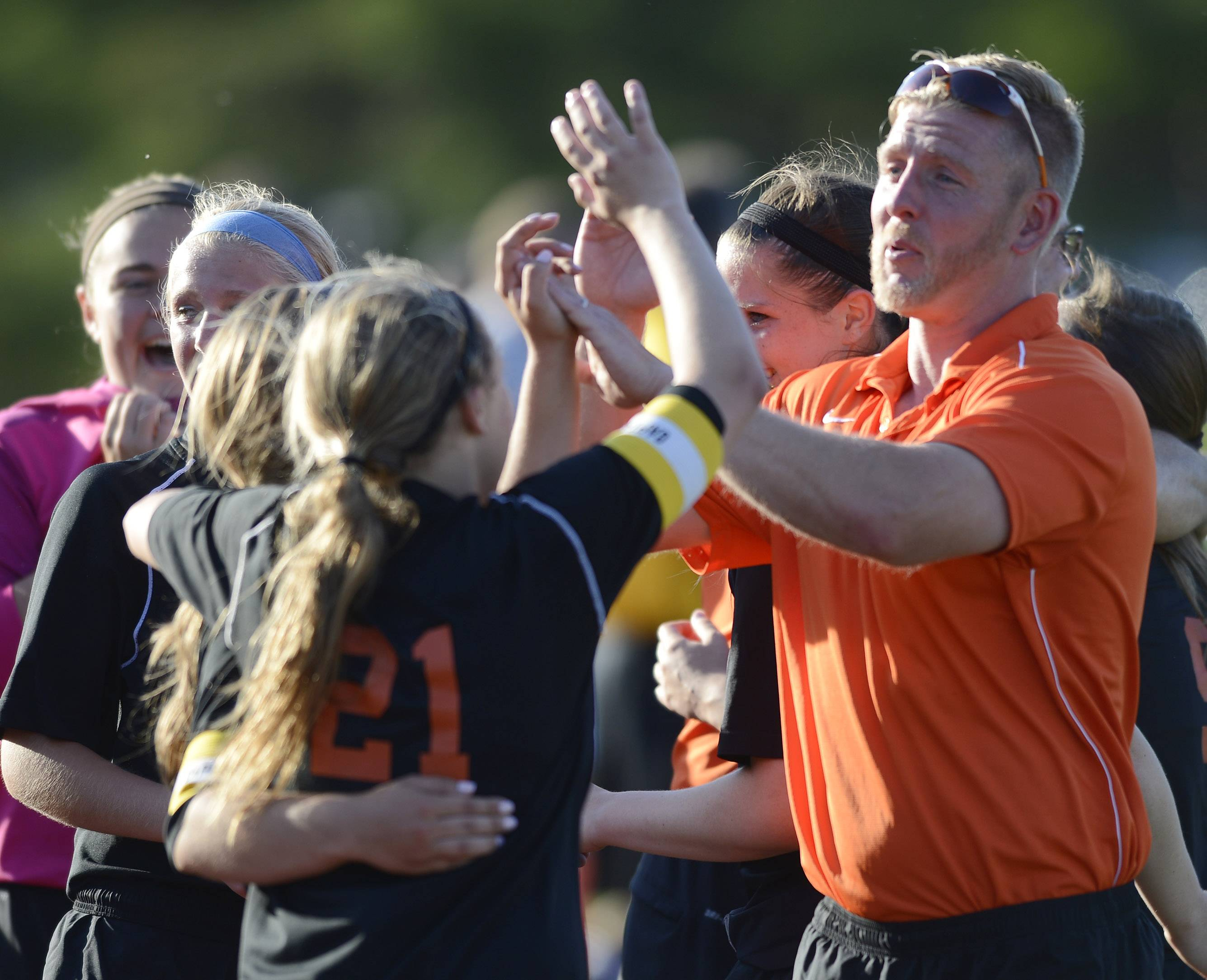 St. Charles East Head coach Paul Jennison congratulates his team for their win over Lincoln Way North during the girls soccer Class 3A state semifinal at North Central College in Naperville Friday.