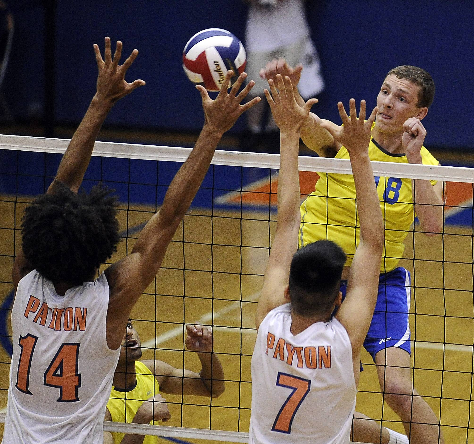 Warren's Jeremy White slams one back to Payton's Earl Schultz and Ryan Krull in set one of the boys volleyball state quarterfinals at Hoffman Estates High School on Friday.