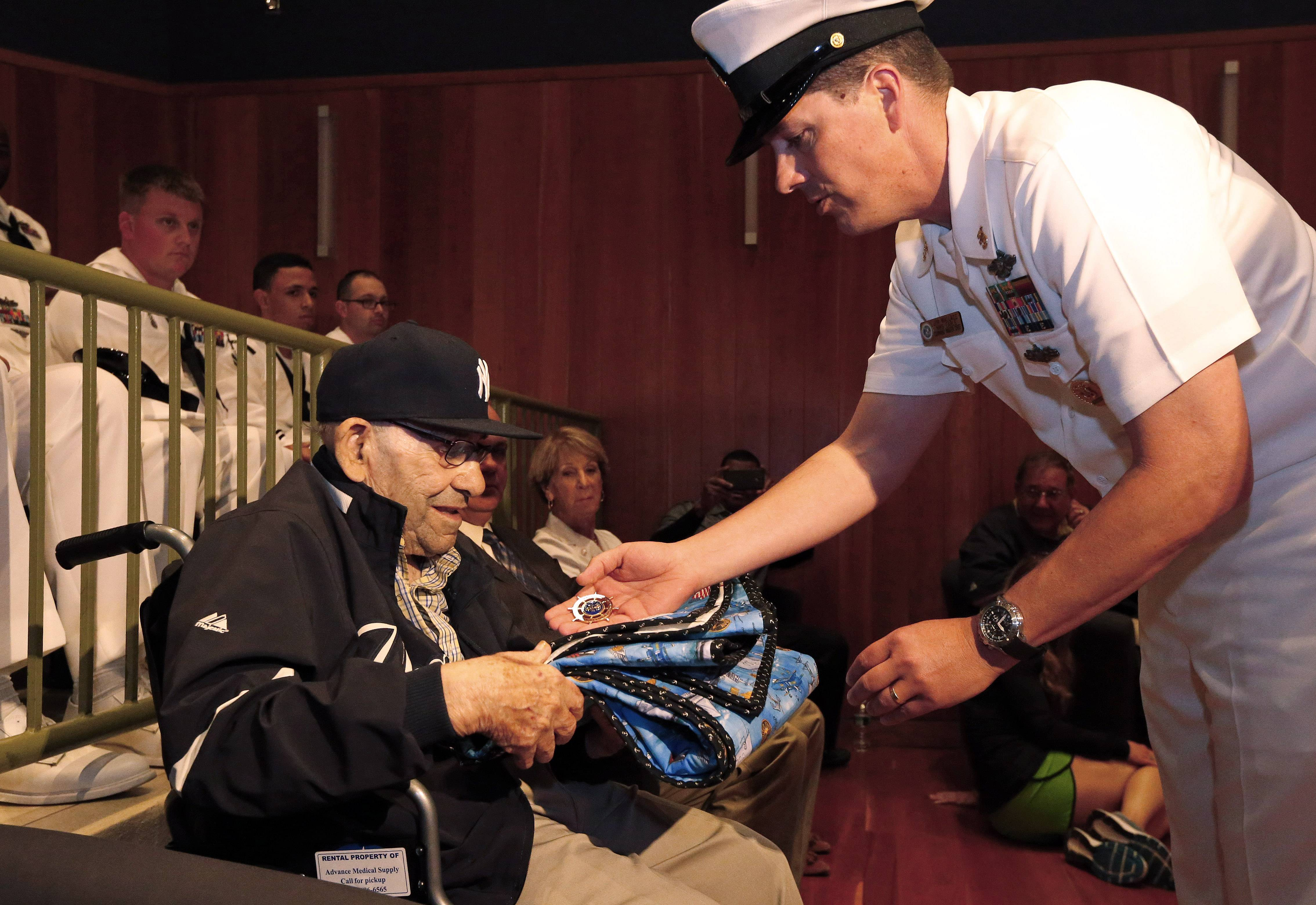 Baseball Hall of Famer Yogi Berra is presented with a quilt and a medal by Cmdr. Jim Wallace during a D-Day presentation at the Yogi Berra Museum in Montclair, N.J., Friday, June 6, 2014. Berra served in the navy 70 years ago as part of the D-Day invasion.