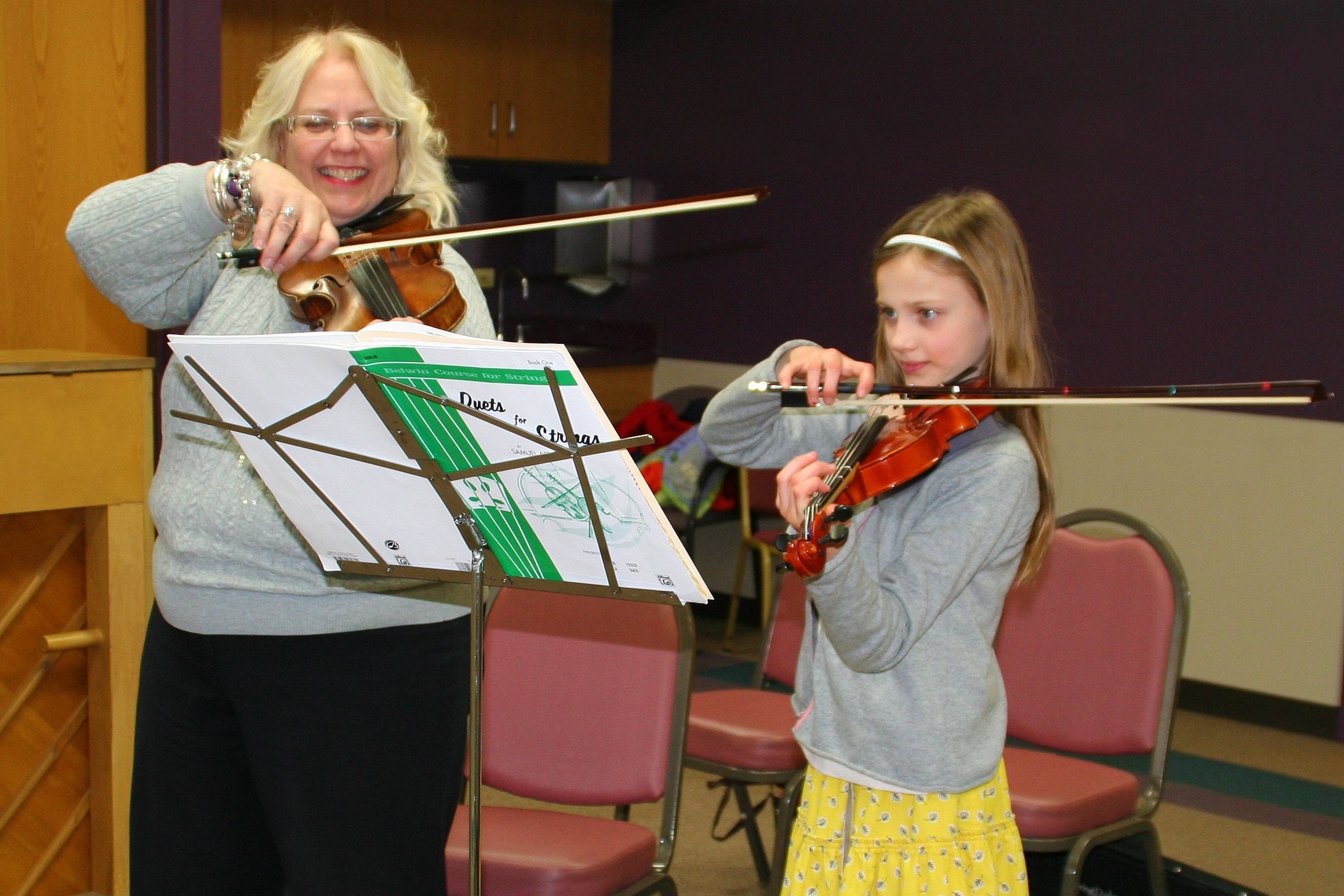 Des Plaines Park District violin instructor, Pam Culley works on a duet for strings with her student.Lisa Haring
