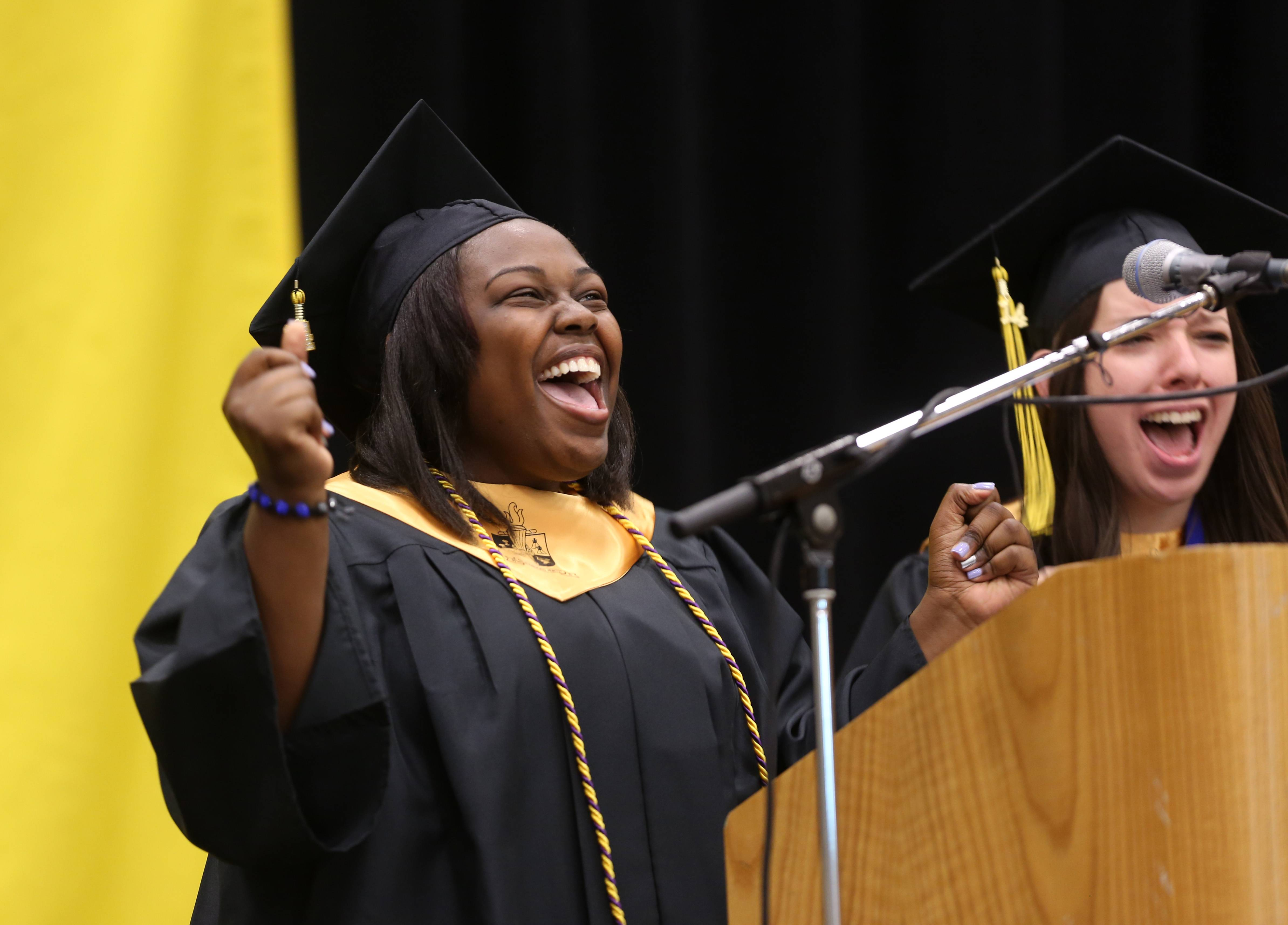 Tia Collins, left, and Lauren Serritella, right, address classmates and their families during the Glenbard North High School graduation at the College of DuPage.