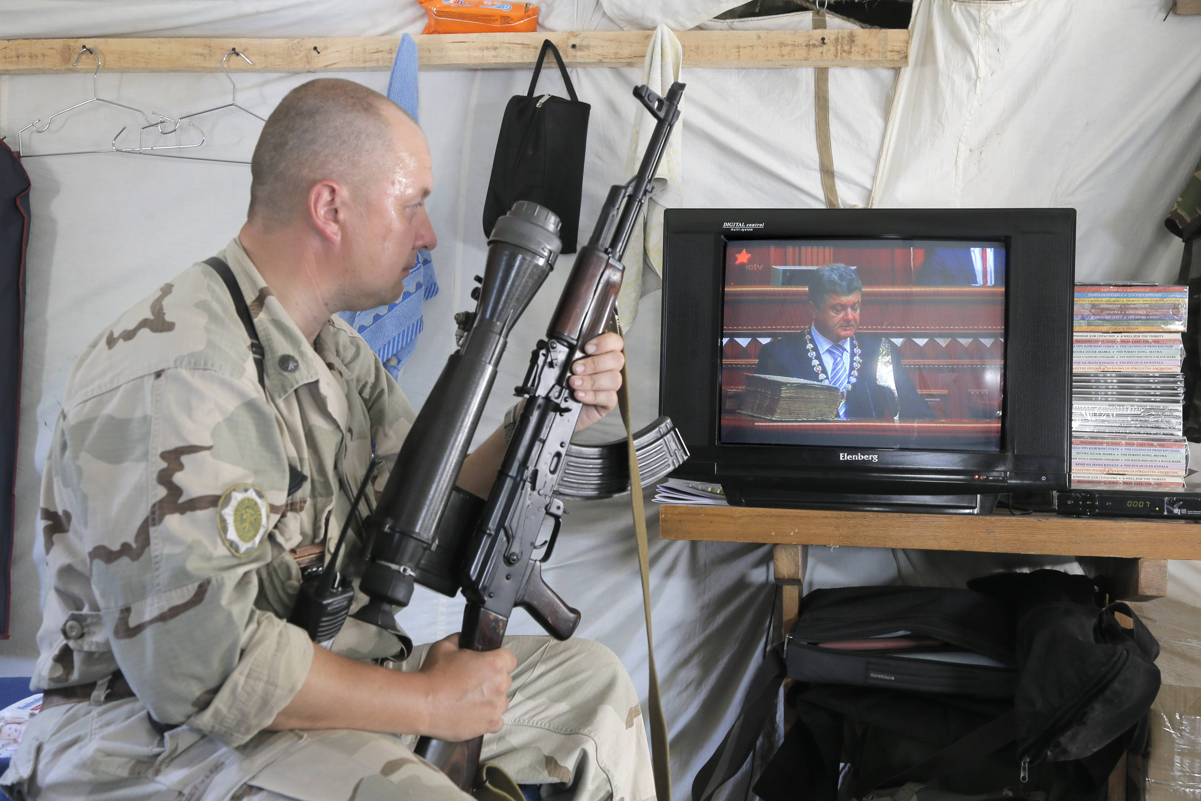A Ukrainian soldier watches the inauguration ceremony Saturday of Ukrainian President-elect Petro Poroshenko on TV in a tent at the Ukraine's Army position close to Slovyansk, Ukraine.
