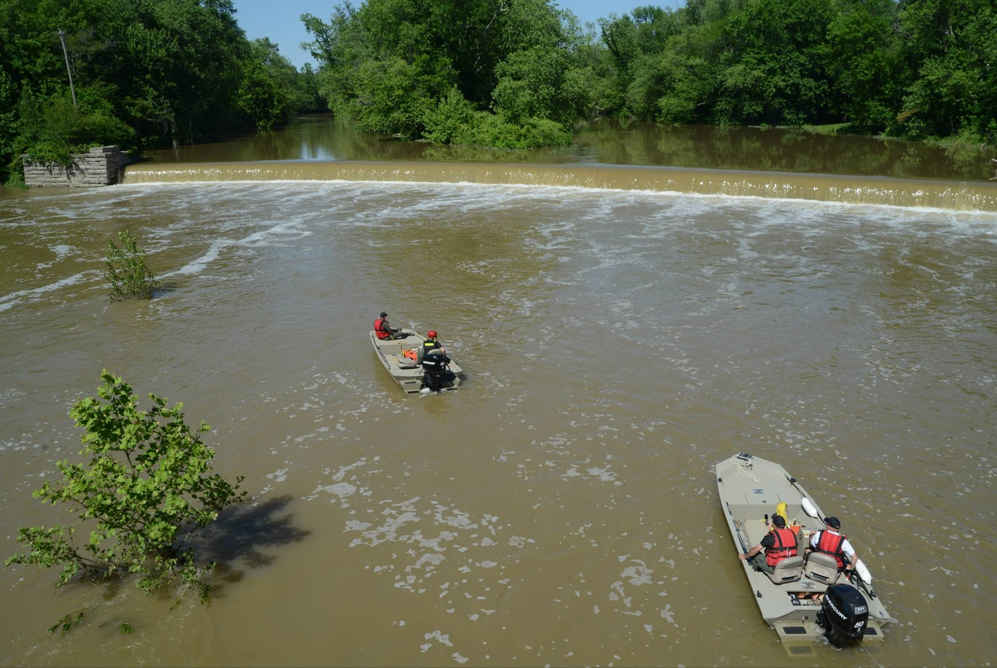 Indiana conservation officers drag the Big Blue River Friday below the dam in Edinburgh, Ind.