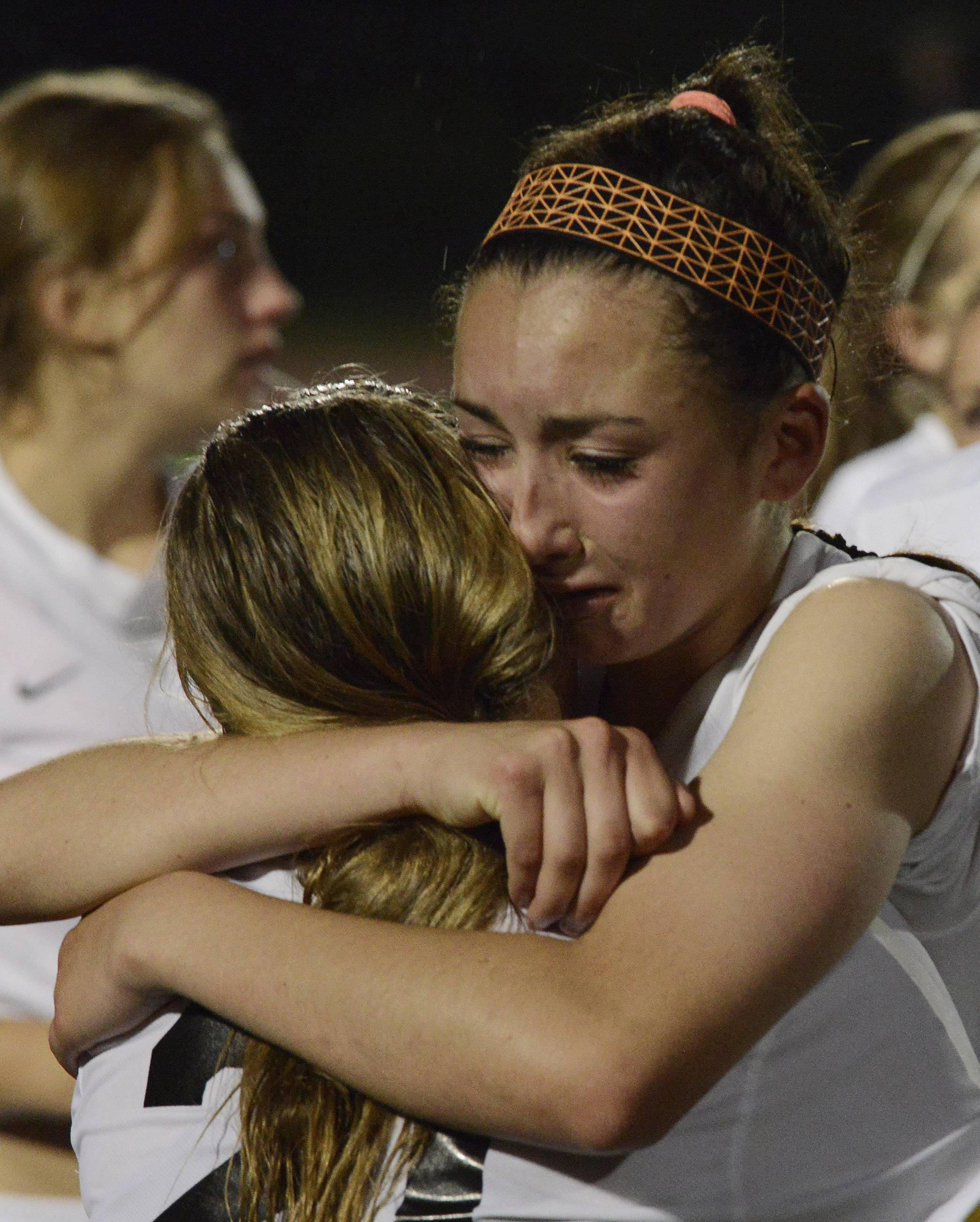 Mallory Moltenhauler, right, of St. Charles East hugs teammate Amanda Hilton following their team's 1-0 loss to New Trier during the girls soccer Class 3A state final at North Central College in Naperville Saturday.