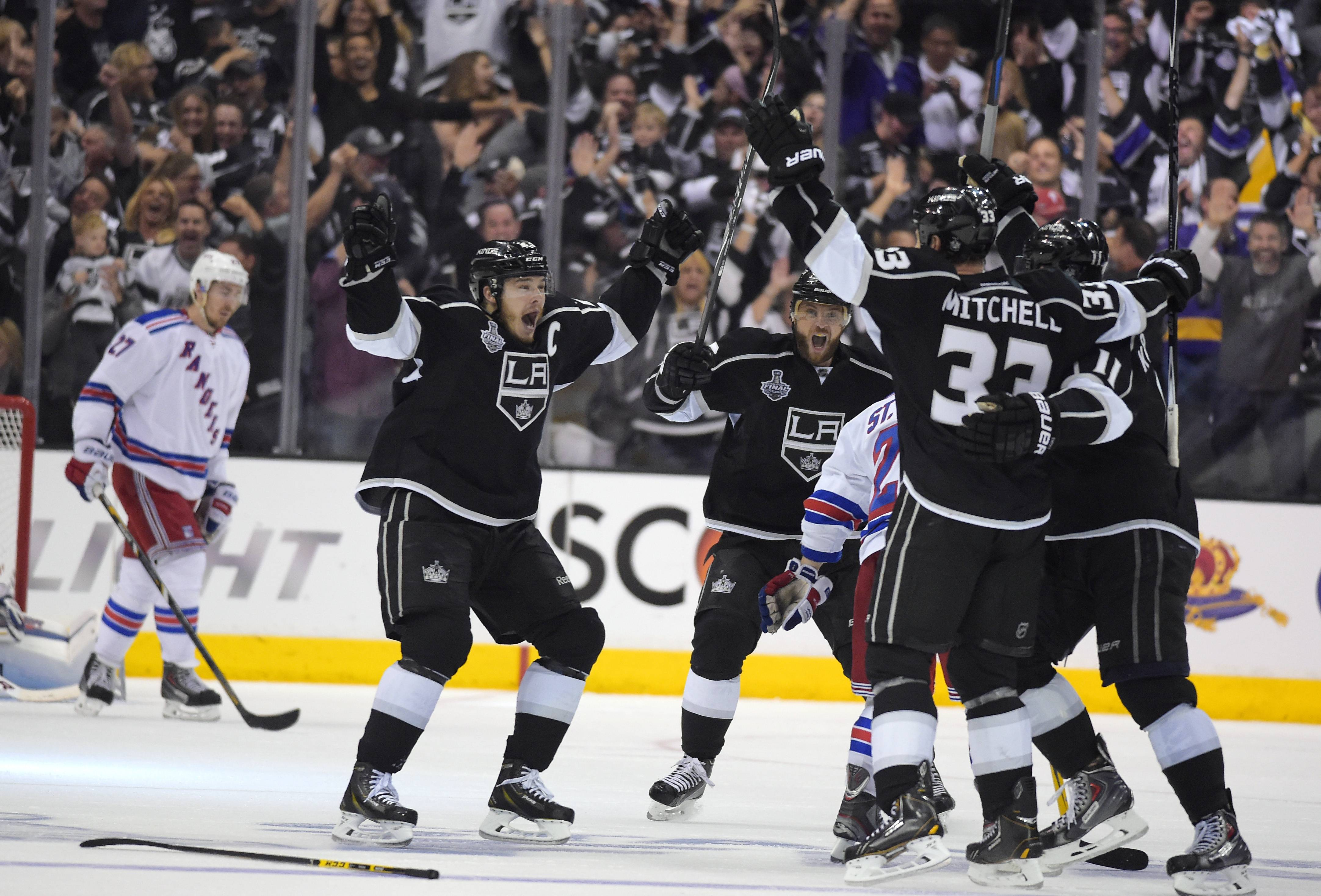 Los Angeles Kings' Dustin Brown, second from left, celebrates his game-winning goal with teammates as New York Rangers defenseman Ryan McDonagh skates at left in the second overtime period in Game 2 of the NHL hockey Stanley Cup Finals, Saturday, June 7, 2014, in Los Angeles. The Kings won 5-4.