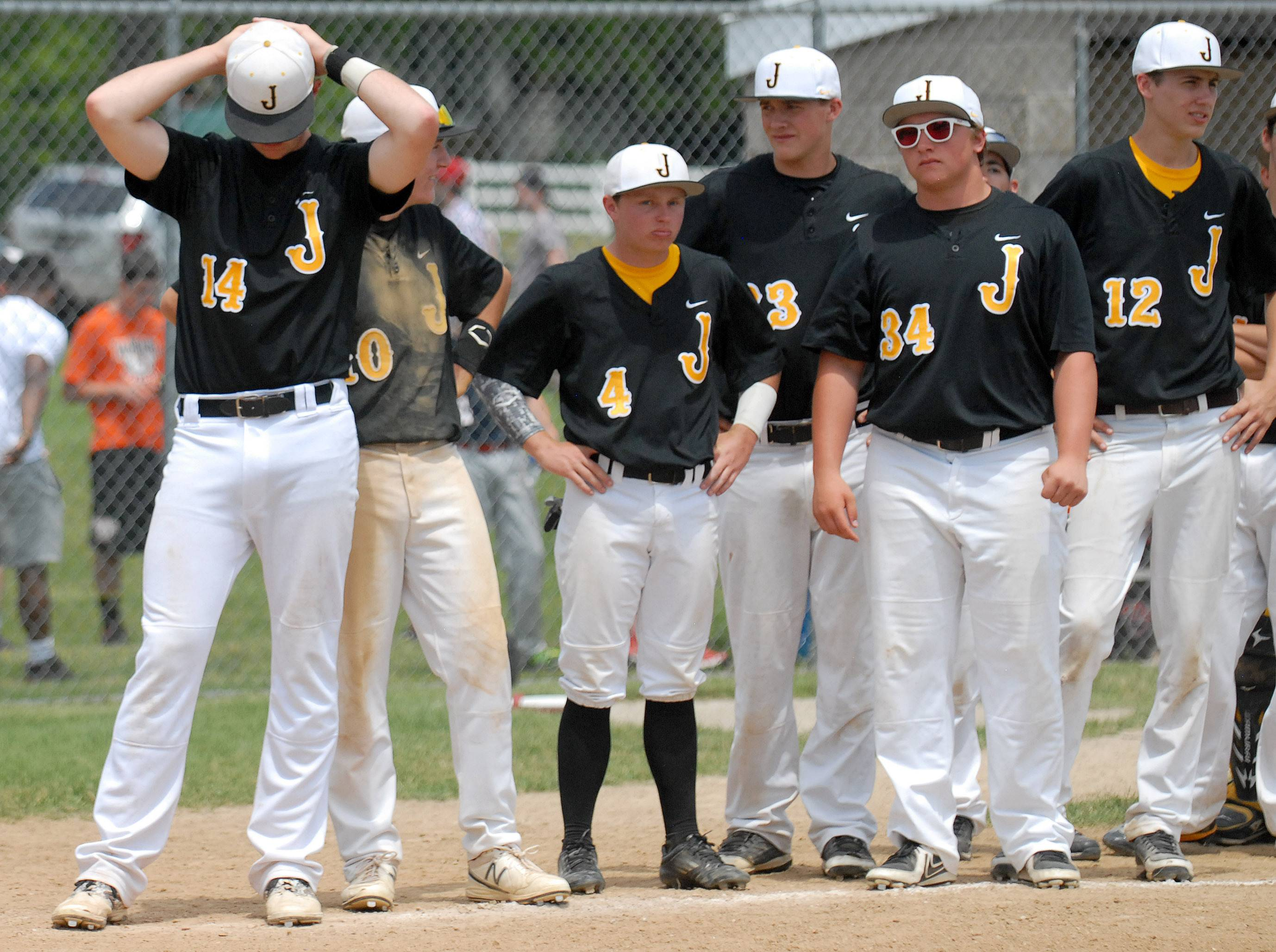 Jacobs' Reilly Peltier (14) and teammates wait at home plate for Prairie Ridge to finish celebrating their Class 4A McHenry sectional championship win at Peterson Park on Saturday.