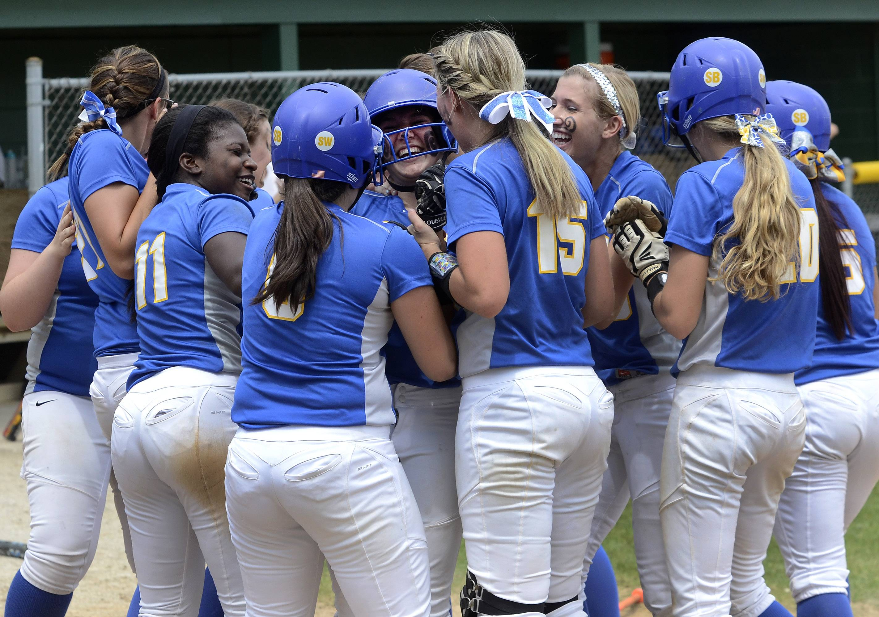 Warren's Rachele Belletini, center, is mobbed after belting a 3-run home run in the fourth inning of the Class 4A Stevenson softball sectional final.