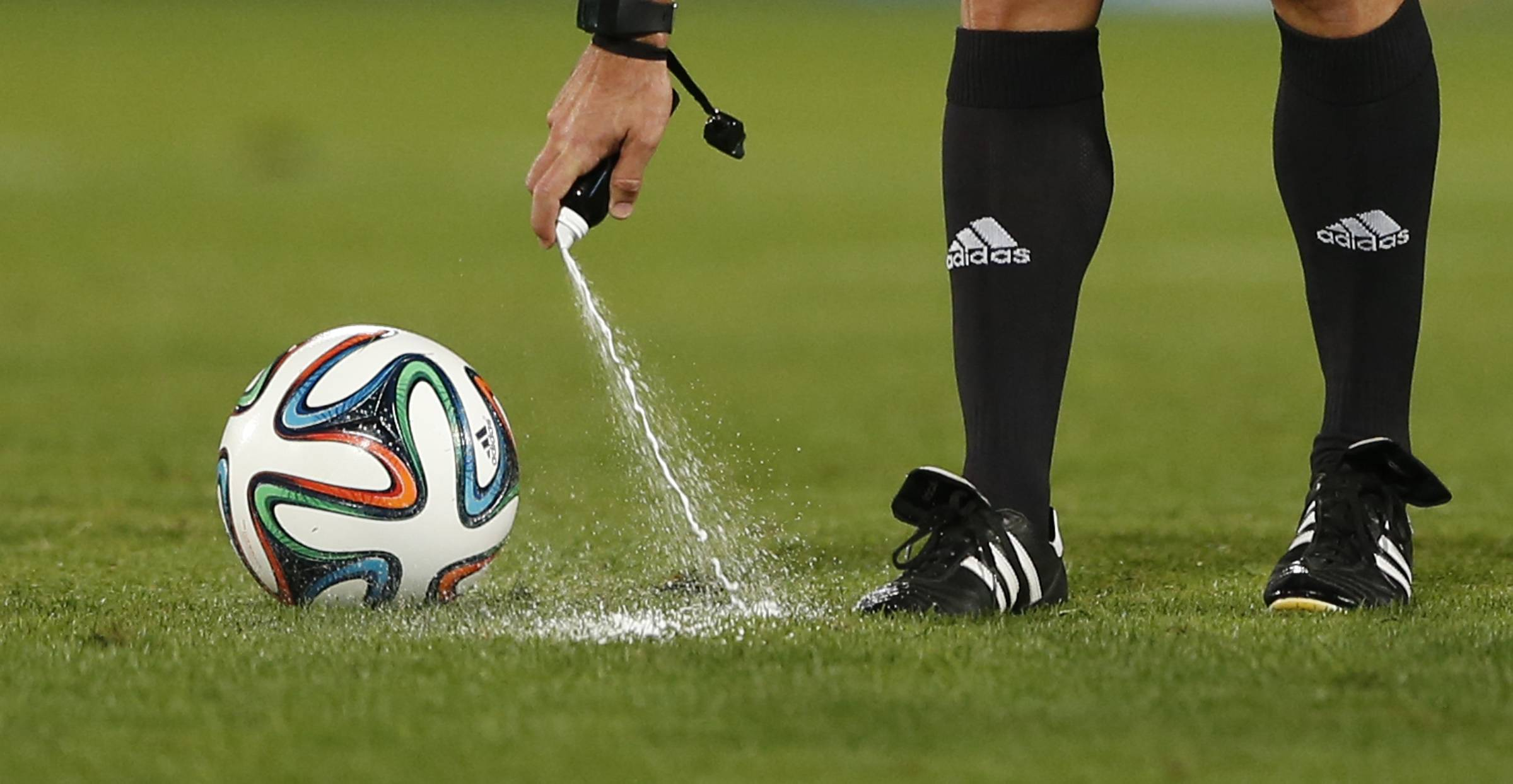 In this Wednesday, Dec. 18, 2013, file photo, referee Carlos Velasco of Spain marks a line with vanishing spray during the semi final soccer match between Raja Casablanca and Atletico Mineiro at the Club World Cup soccer tournament in Marrakech, Morocco. For the first time at a World Cup, technology will be used to determine whether a ball crosses the goal line during matches at the upcoming tournament in Brazil.