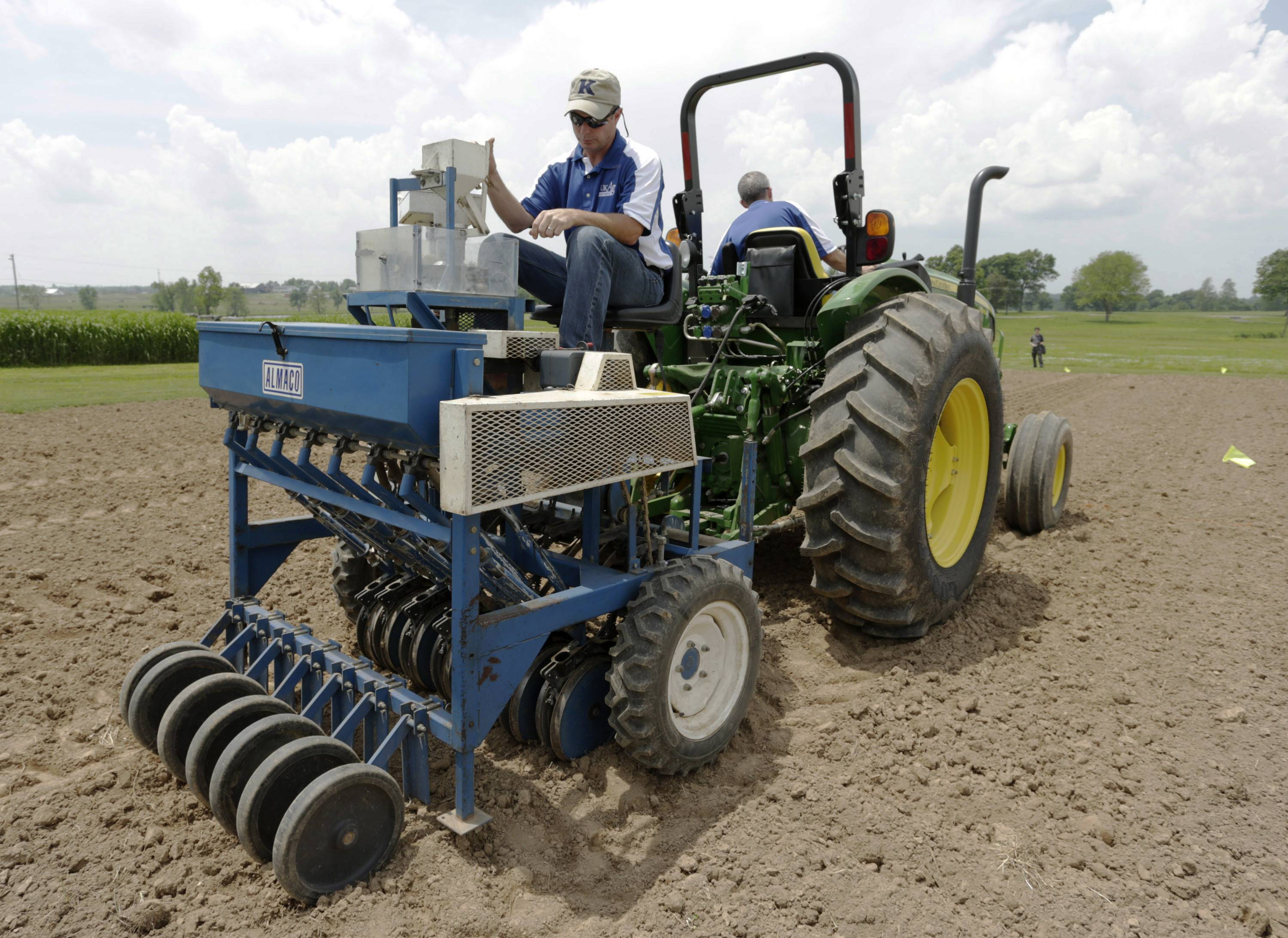 Richard Mundell sits on a plot seeder pulled by a tractor driven by Mark Sizemore, as they plant hemp seeds last month at the UK Spindletop Research Farm off of Newtown Pike in Lexington, Ky.